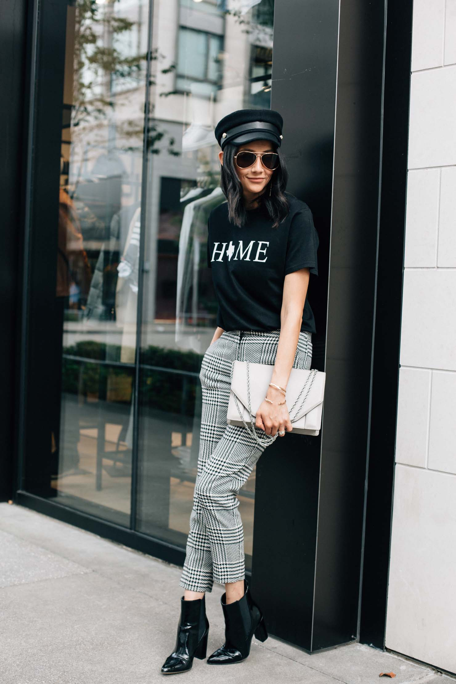 Lilly Beltran of Daily Craving blog in a chic fall outfit with black Chelsea boots, plaid pants and a baker boy hat