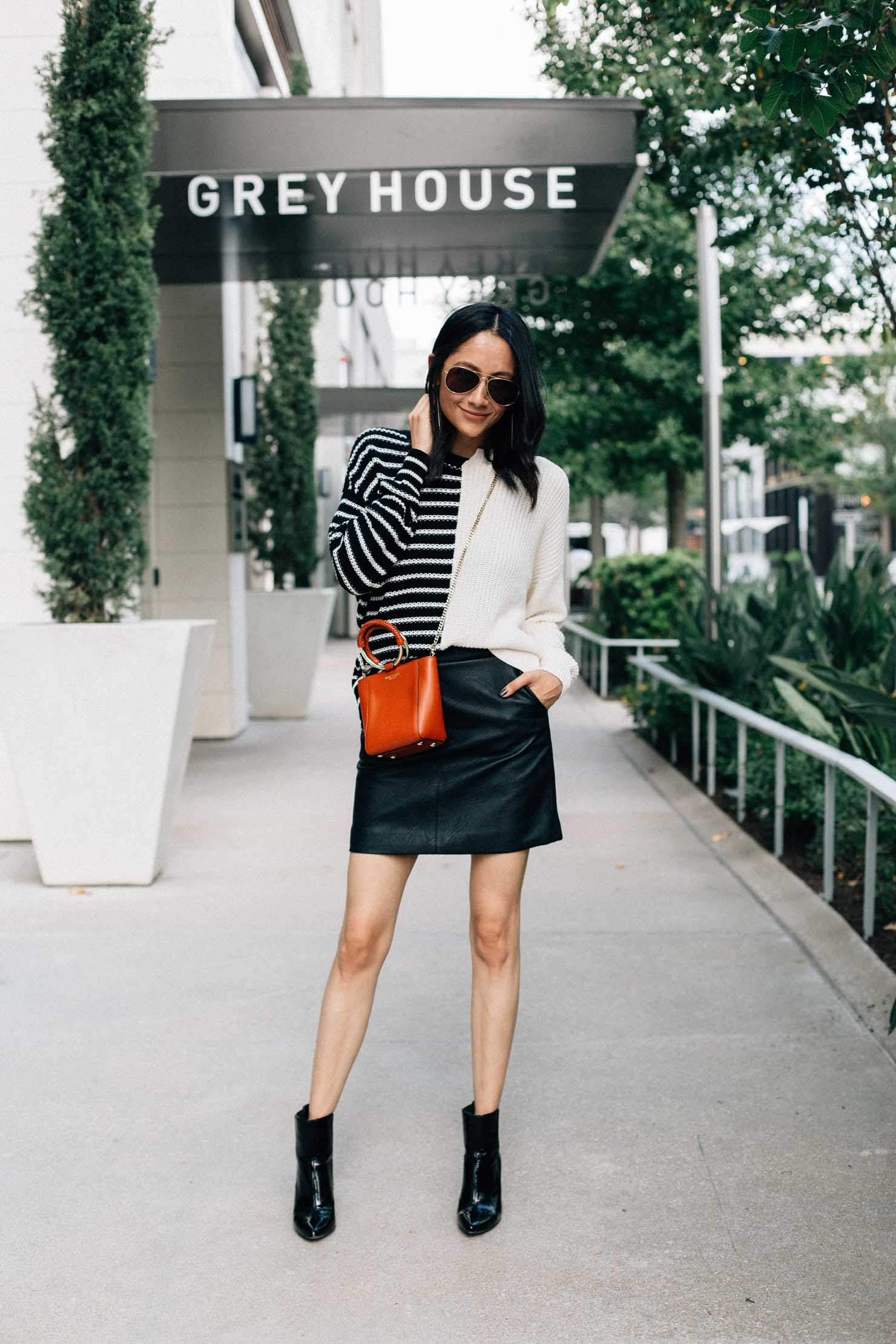 Lilly Beltran of Daily Craving blog wearing a faux leather skirt with a color blocked sweater and black ankle boots