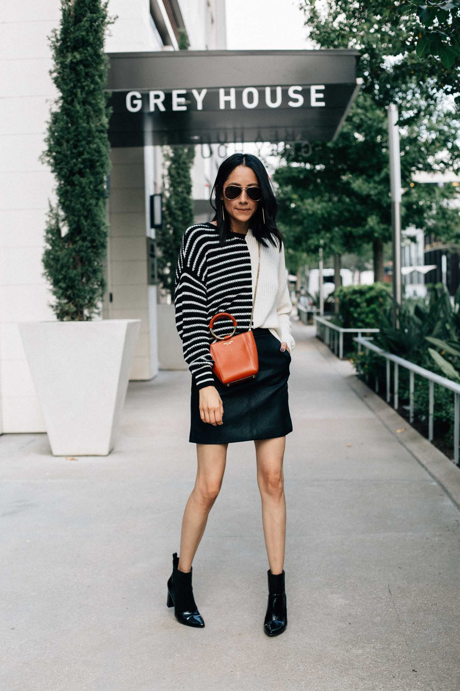 Style blogger Lilly Beltran of Daily Craving in a black leather skirt, oversized striped sweater and black patent leather boots