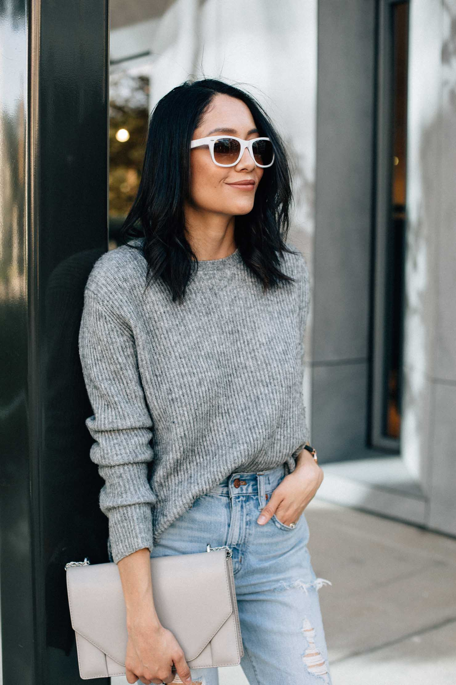 Lilly Beltran of Daily Craving wearing an oversized grey sweater, white frame sunglasses and vintage denim for a casual fall outfit