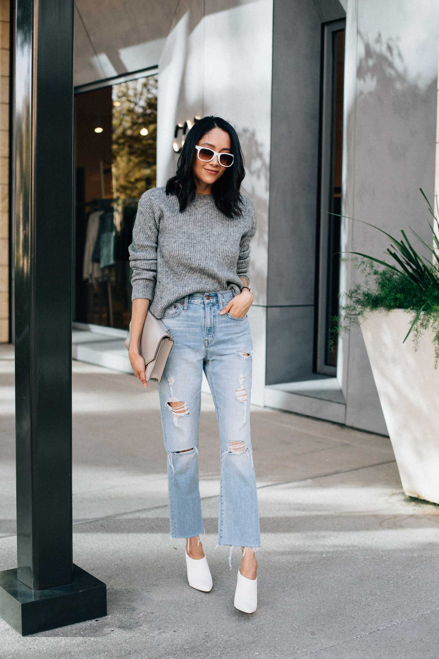 Lilly Beltran of Daily Craving in a casual fall outfit with ripped jeans, oversized sweater and white mules