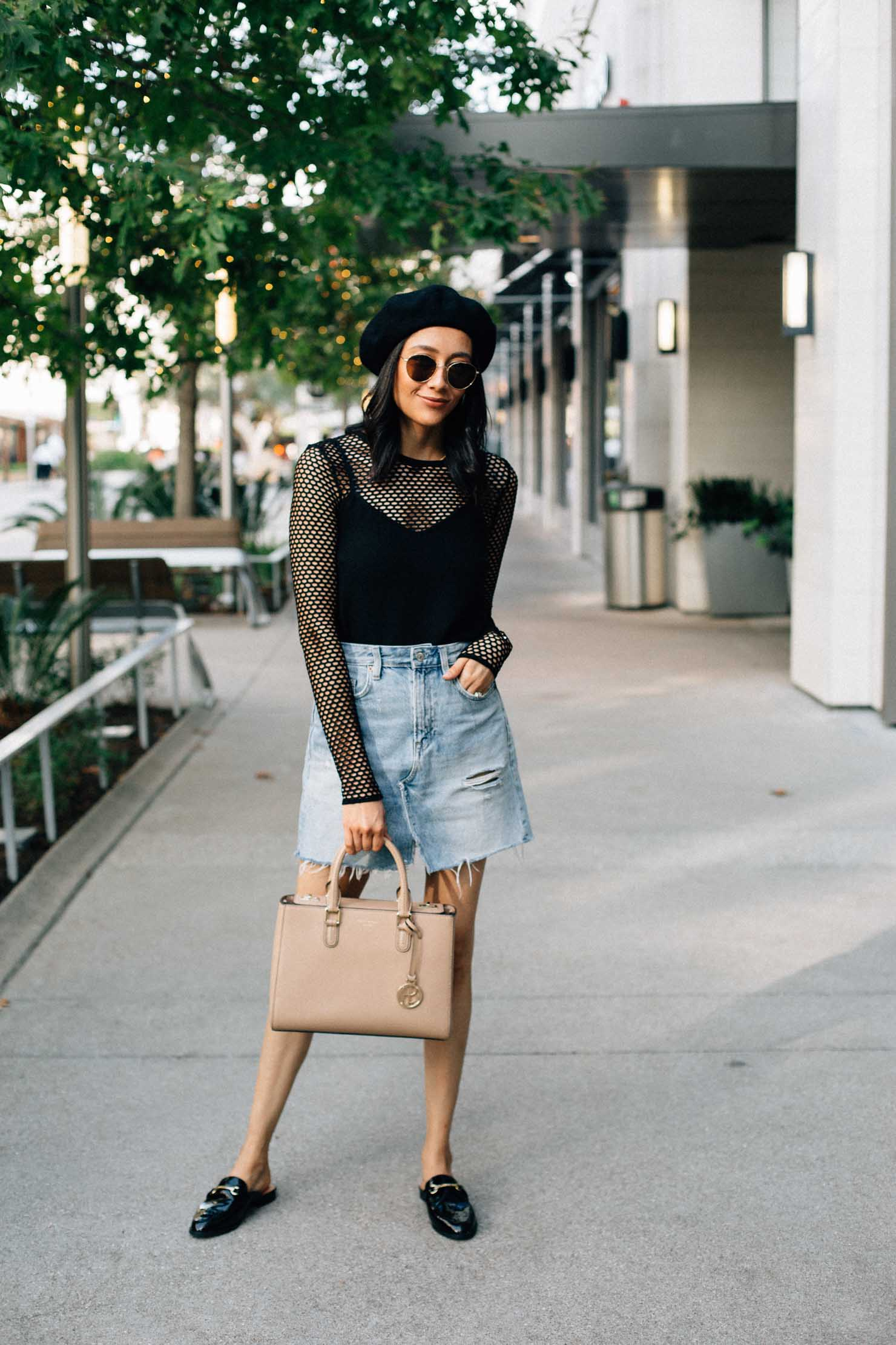 Lilly Beltran of Daily Craving in a casual fall outfit with a black mesh top, a denim skirt, loafer mules and a black beret
