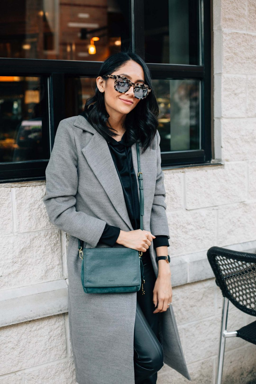 Fashion blogger Daily Craving styles leather leggings with nike sneakers & and maxi coat