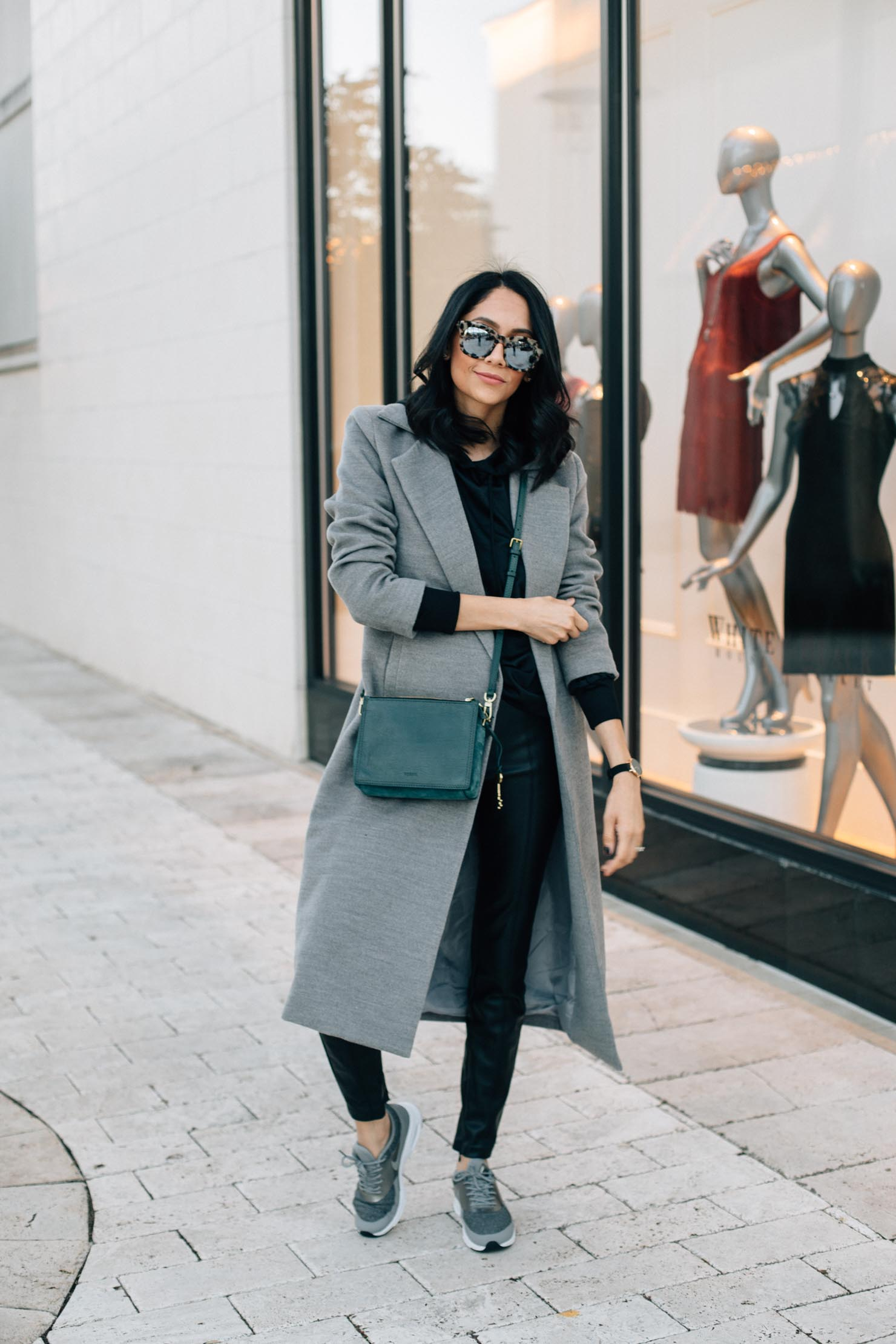 Houston based fashion blogger Lilly Beltran of Daily Craving wears leather black leggings with grey Nike sneakers, long grey coat & green suede fossil watch for a casual chic winter look