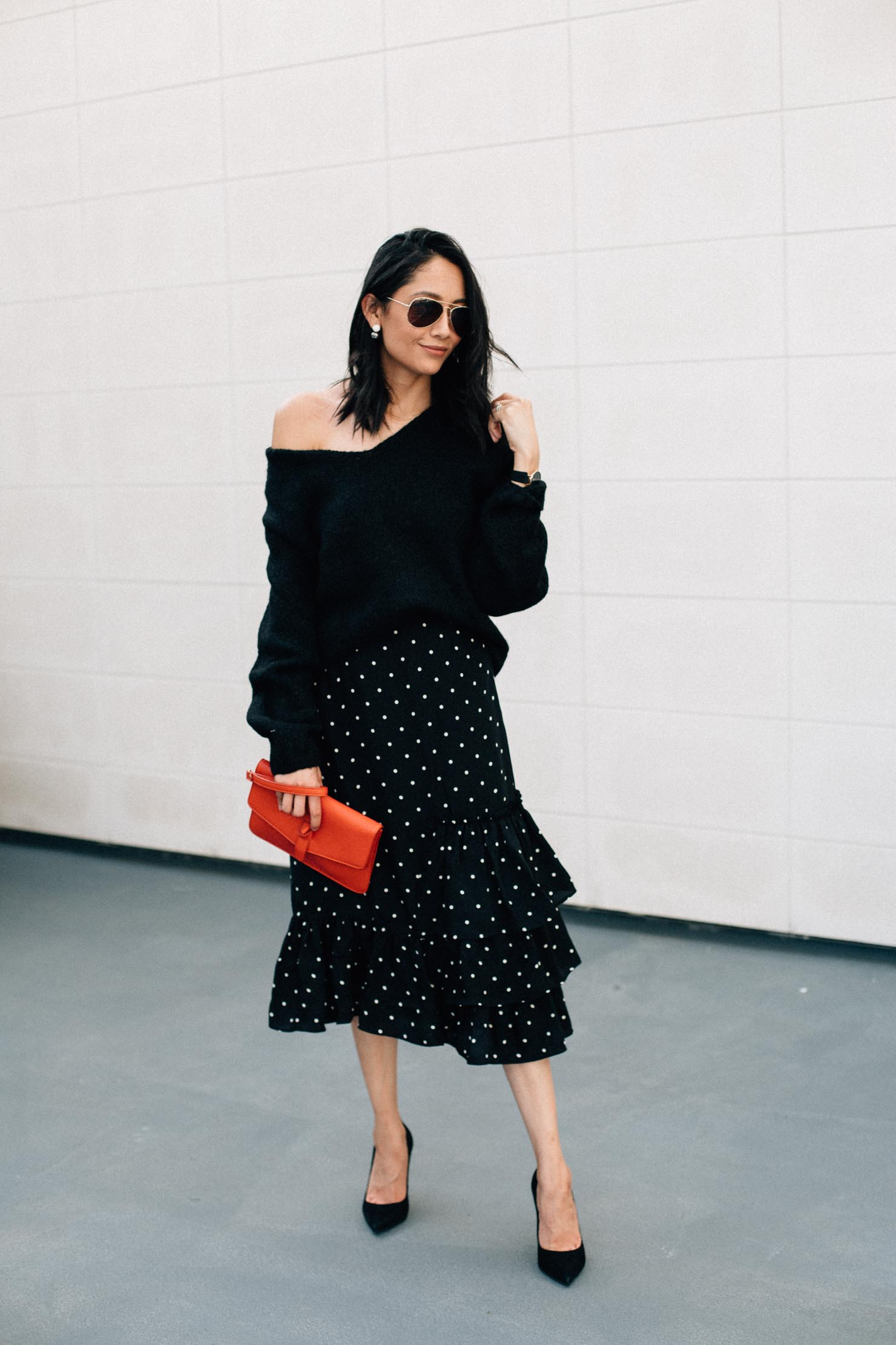 Thanksgiving Outfit Idea. Black oversized sweater, polka dot midi skirt, suede pumps and red clutch