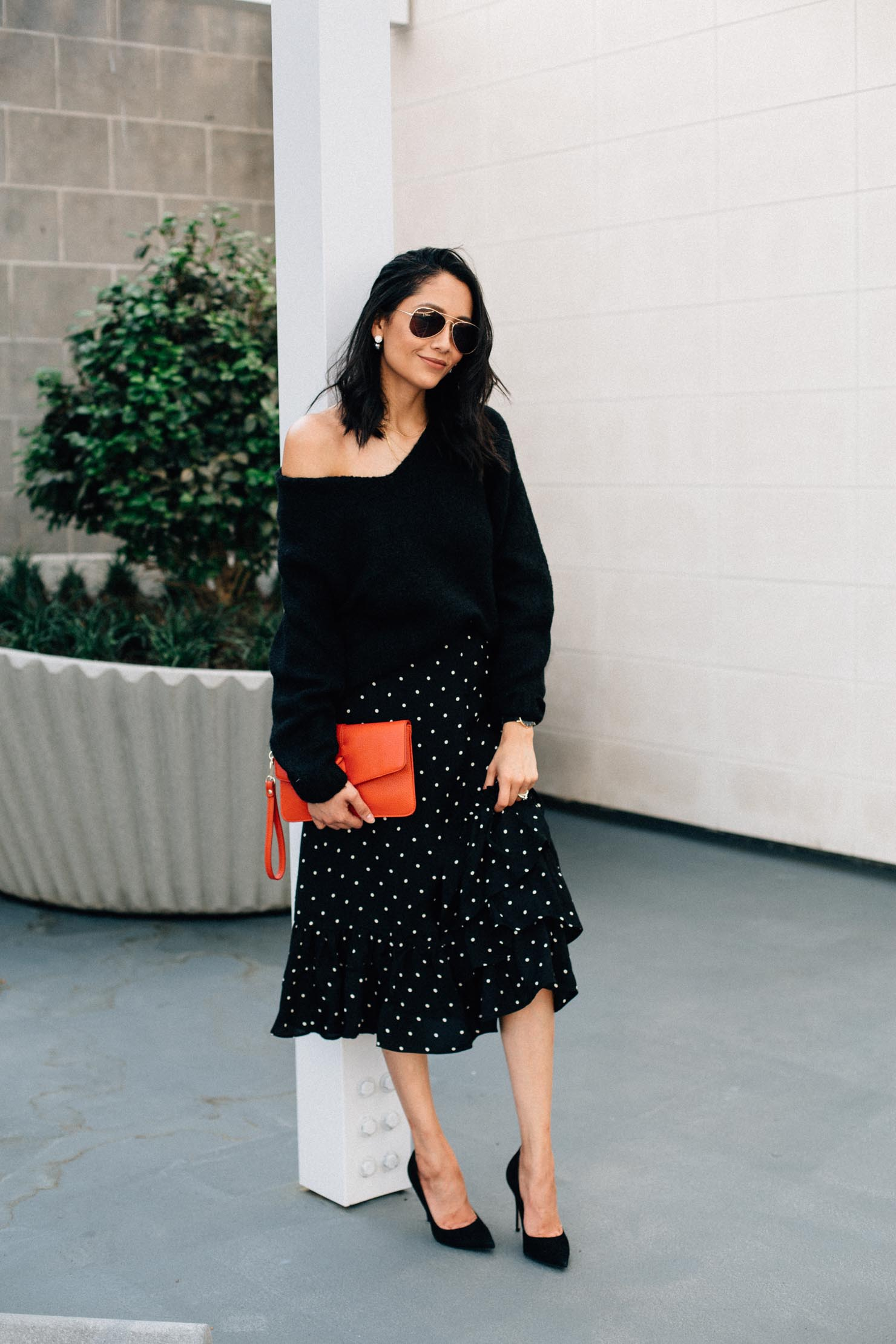 Thanksgiving outfit idea from fashion blogger Lilly Beltran with a black polka dot midi skirt, black chunky sweater & red clutch