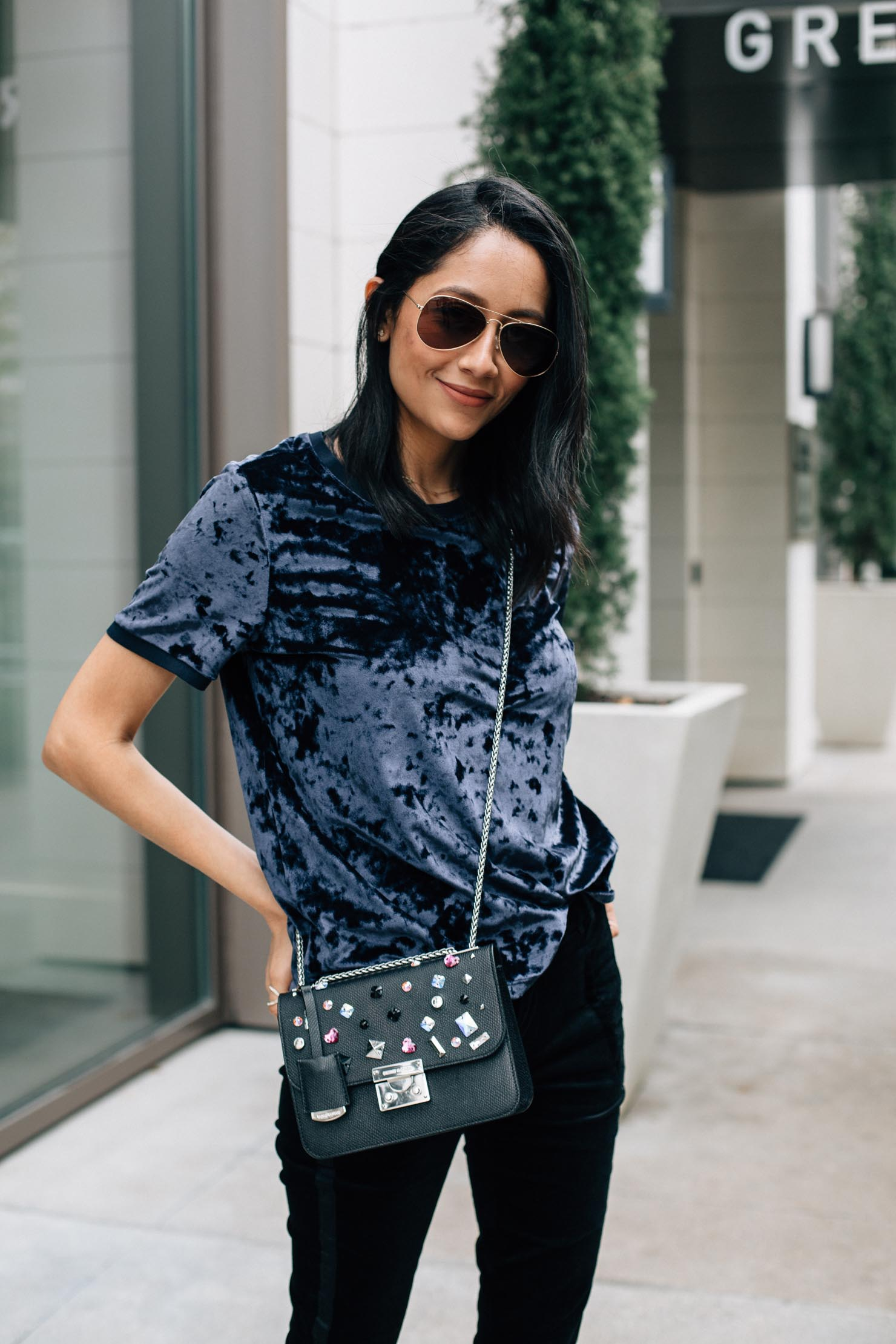 Style blogger Lilly Beltran of Daily Craving wearing a blue crushed velvet top with black velvet pants and a bejeweled Henri Bendel Bag for a causal holiday outfit