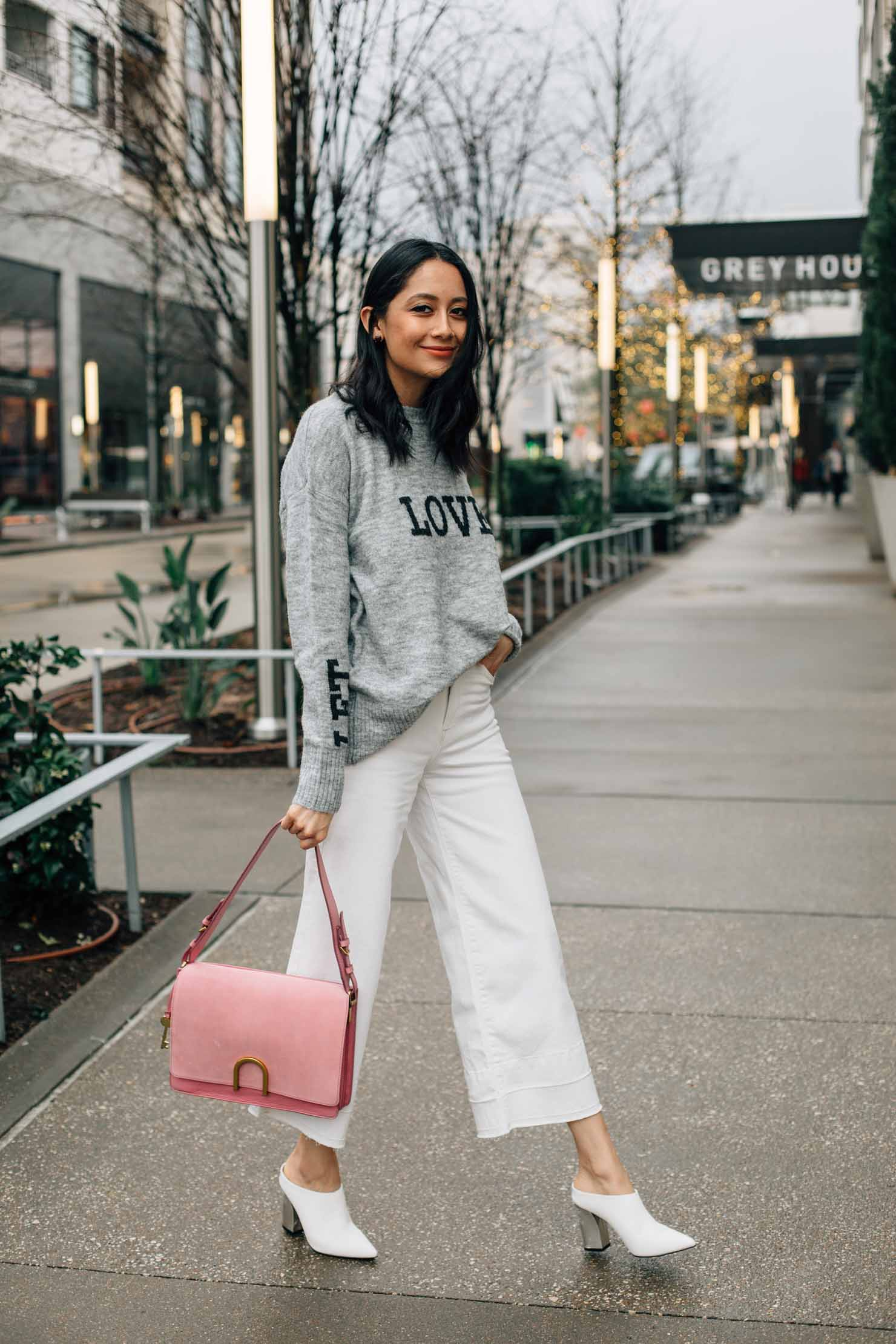 Lilly Beltran of Daily Craving blog in white wide leg denim, grey printed sweater, white mules & pink Fossil bag