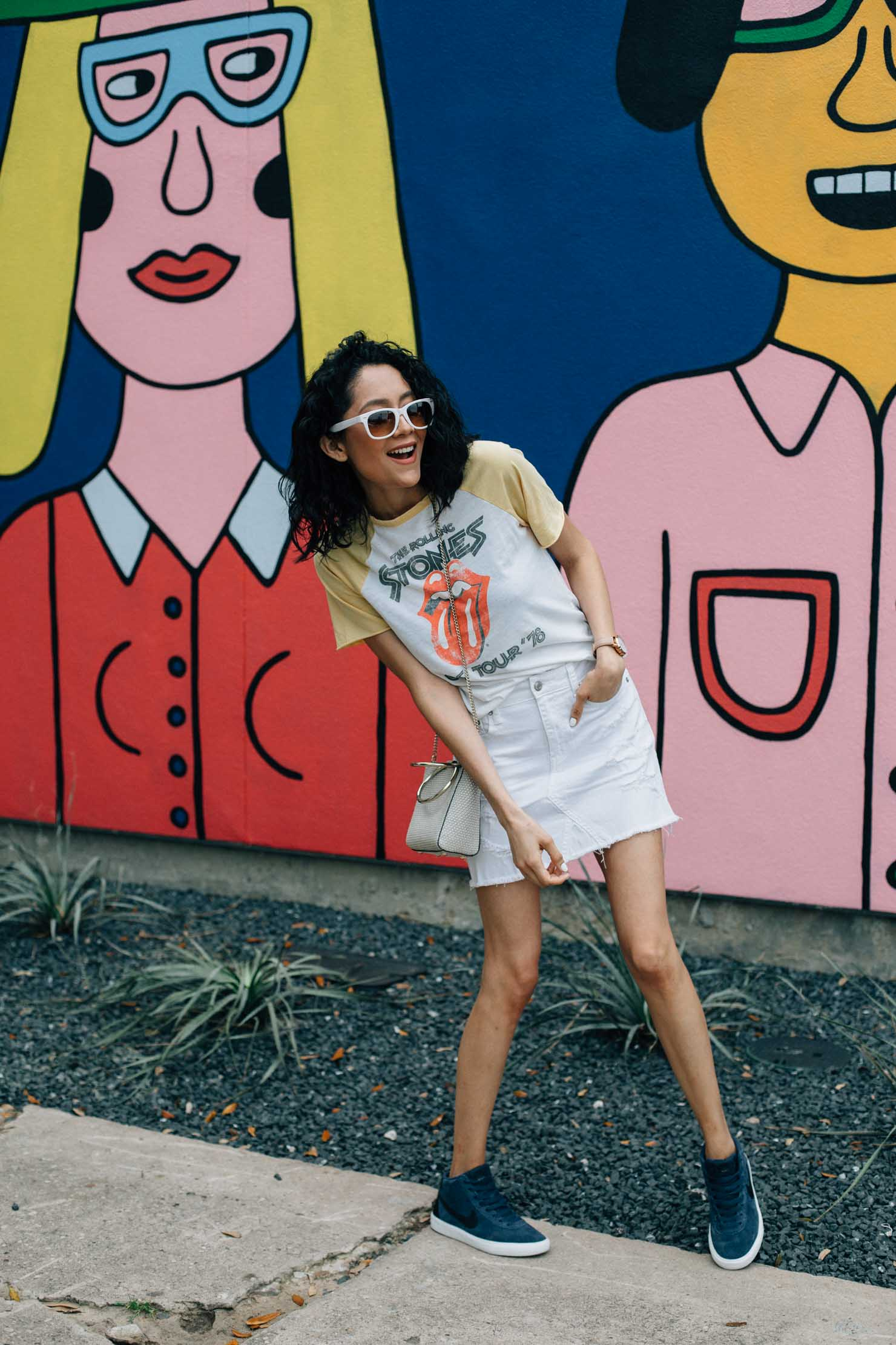 Lilly Beltran Houston Based fashion blogger wearing Rolling Stones tee with a white denim skirt and hightop nike sneakers