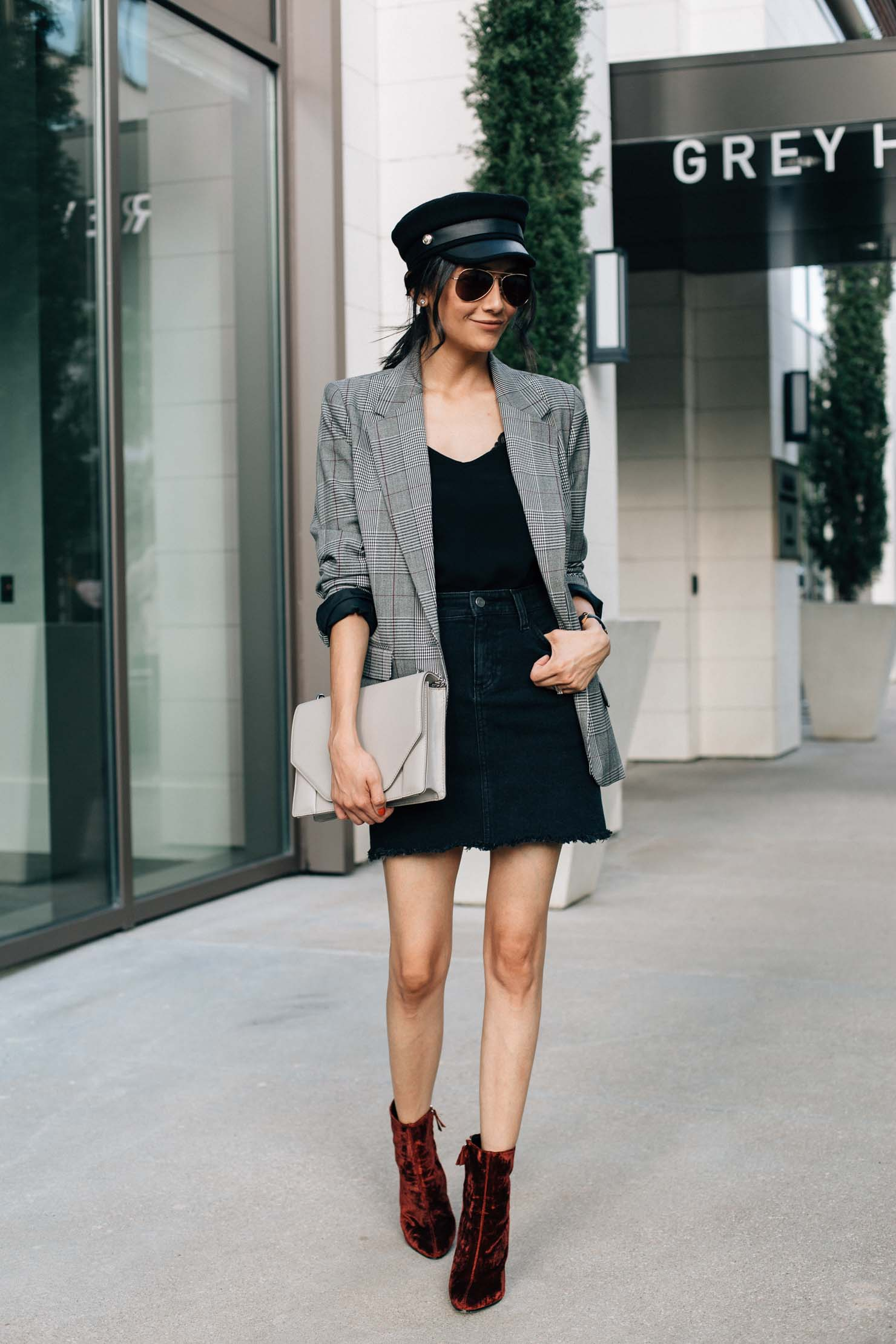 fashion blogger Lilly Beltran styles a black denim skirt with a plaid blazer and velvet booties for a chic street style look