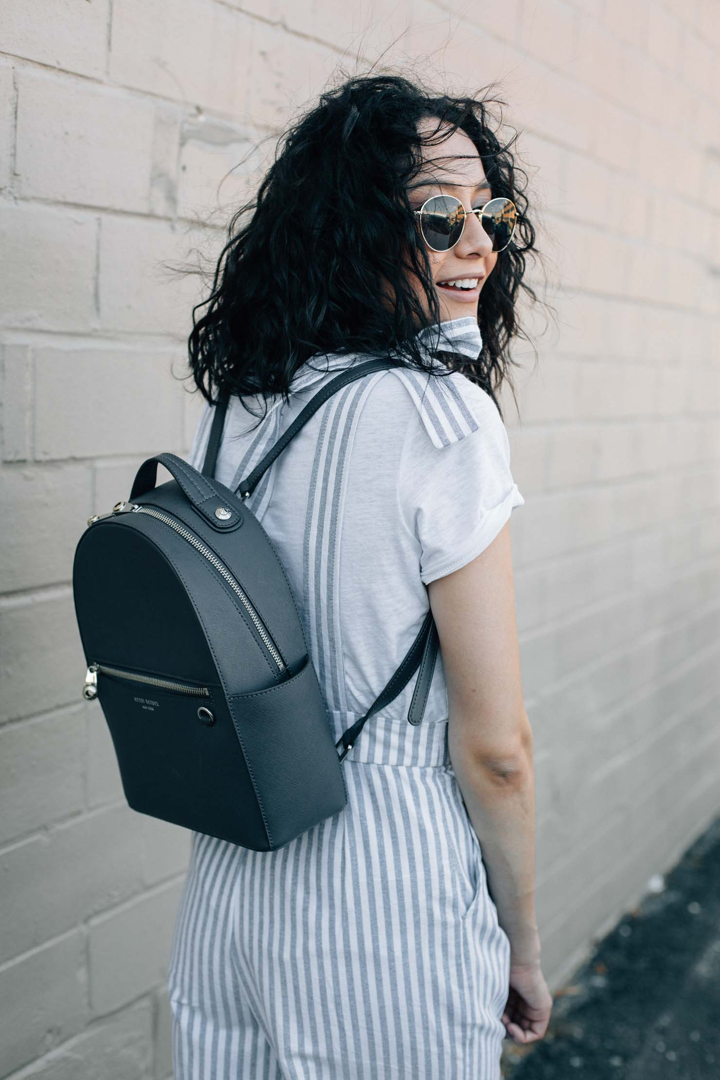 Lilly Beltran of Daily Craving in a striped jumpsuit with a Henri Bendel Backpack | Jumpsuits for Spring
