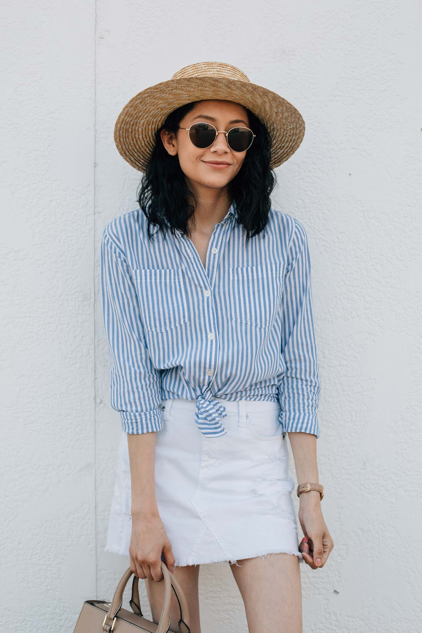 Lilly Beltran of Daily Craving fashion blog wearing a white denim skirt with a blue striped shirt and wide brim fedora