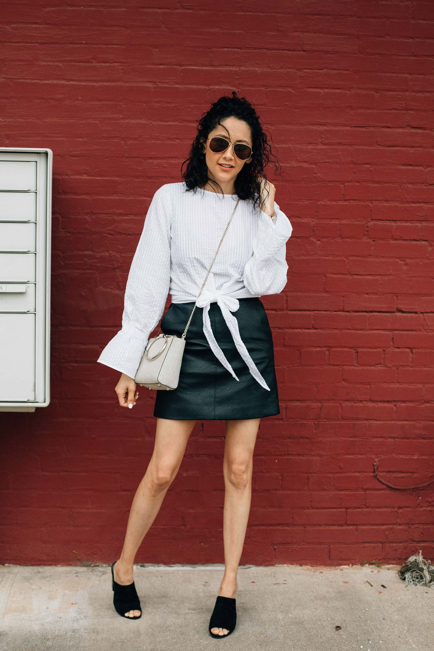 Houston based fashion blogger wearing H&M front tie shirt with leather mini skirt and black mules for a chic streetwear look