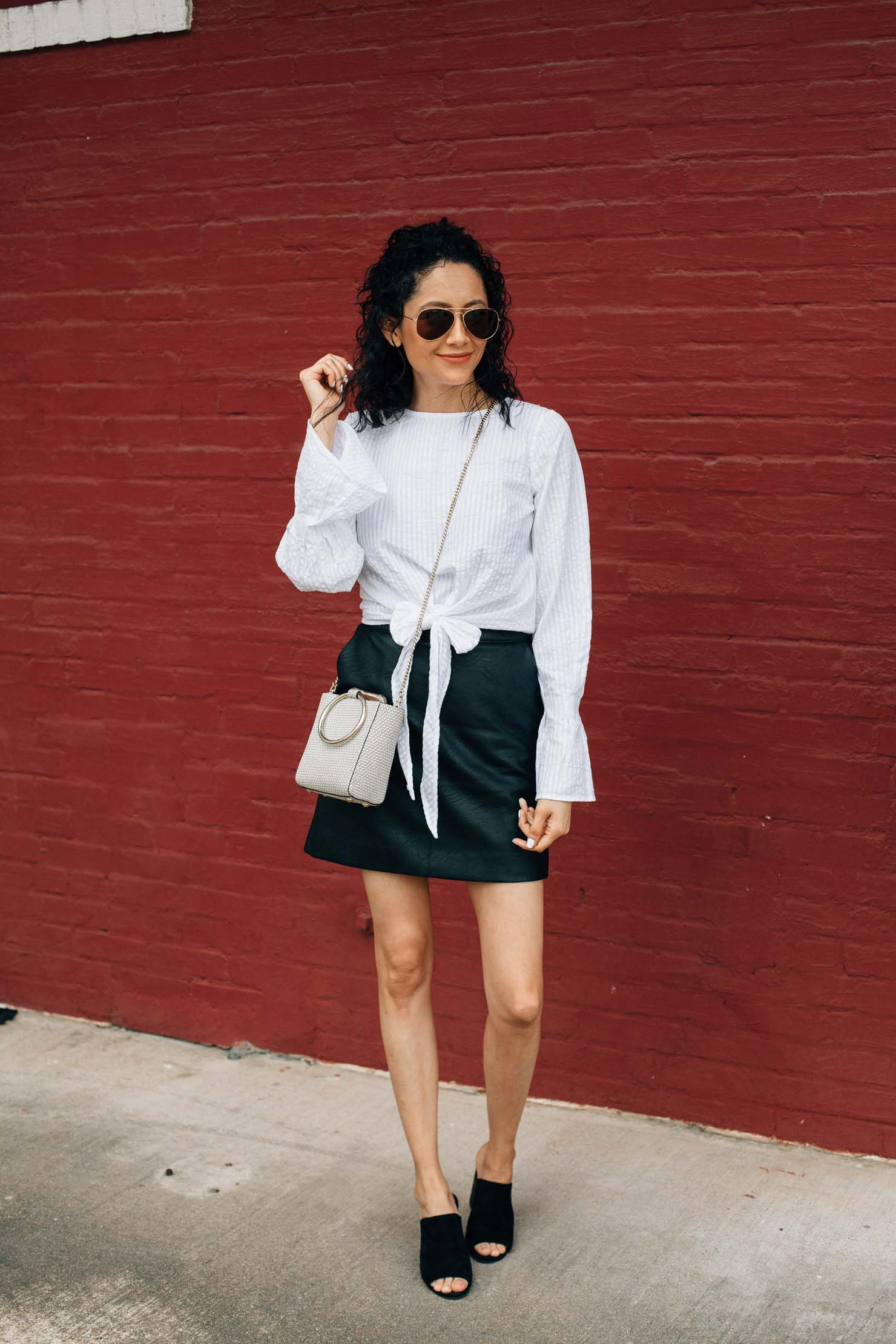 Lilly Beltran in a white front tie top with a black faux leather skirt, black mules and Henri Bendel Bag