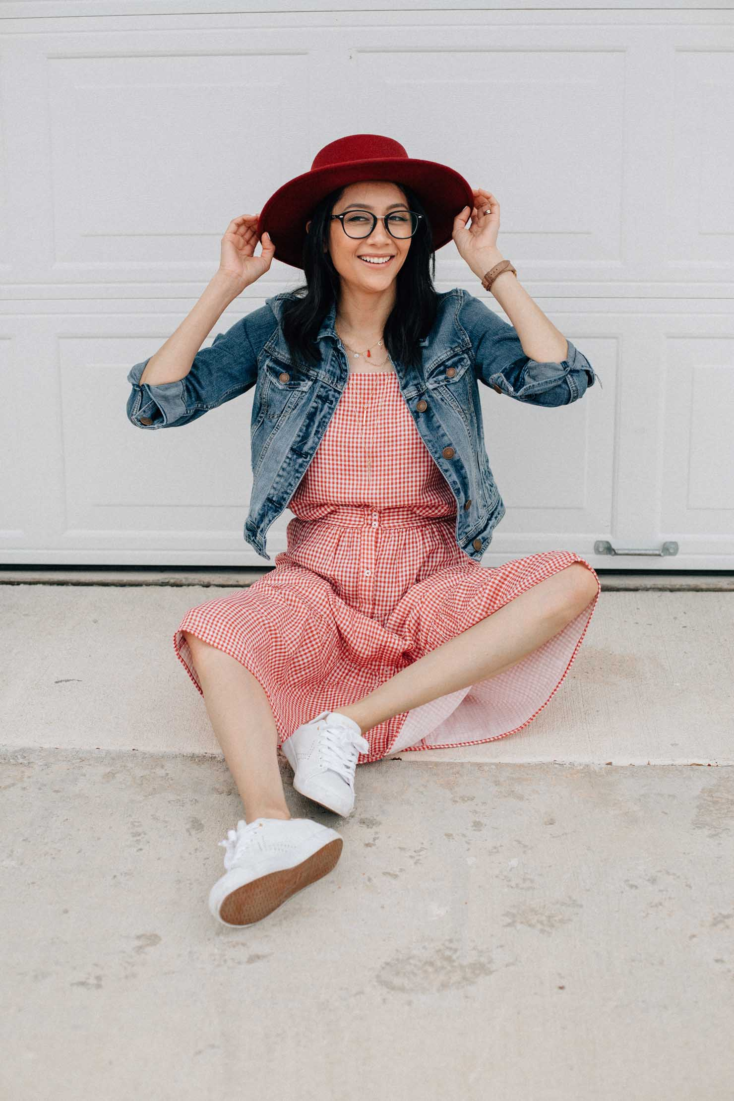 Houston based fashion blogger Lilly Beltran in a red gingham set with white sneakers and denim jacket