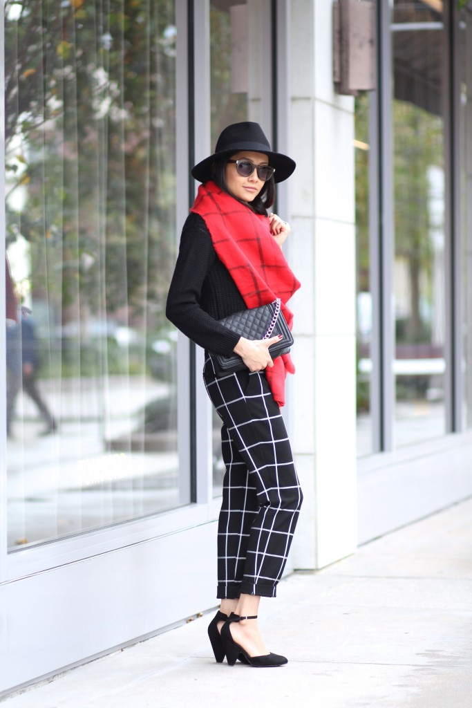 Matching patterns- black plaid pants, black sweater and red plaid scarf.