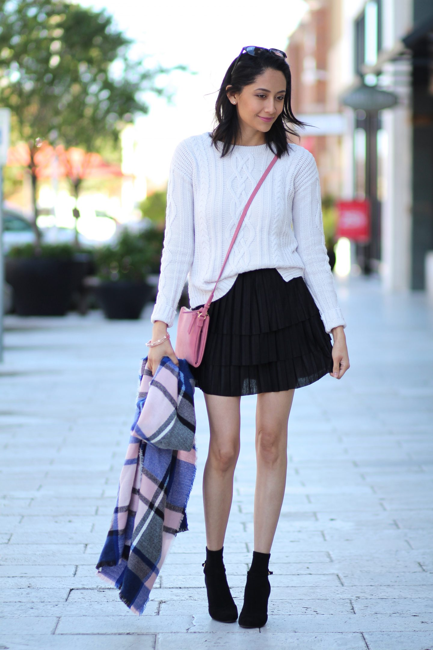 Fashion blogger Daily Craving in a casual holiday outfit with a cable knit sweater and pleated skirt