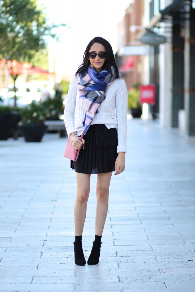Fashion blogger Lilly Beltran in a casual fall look with a plated mini skirt and plaid blanket scarf