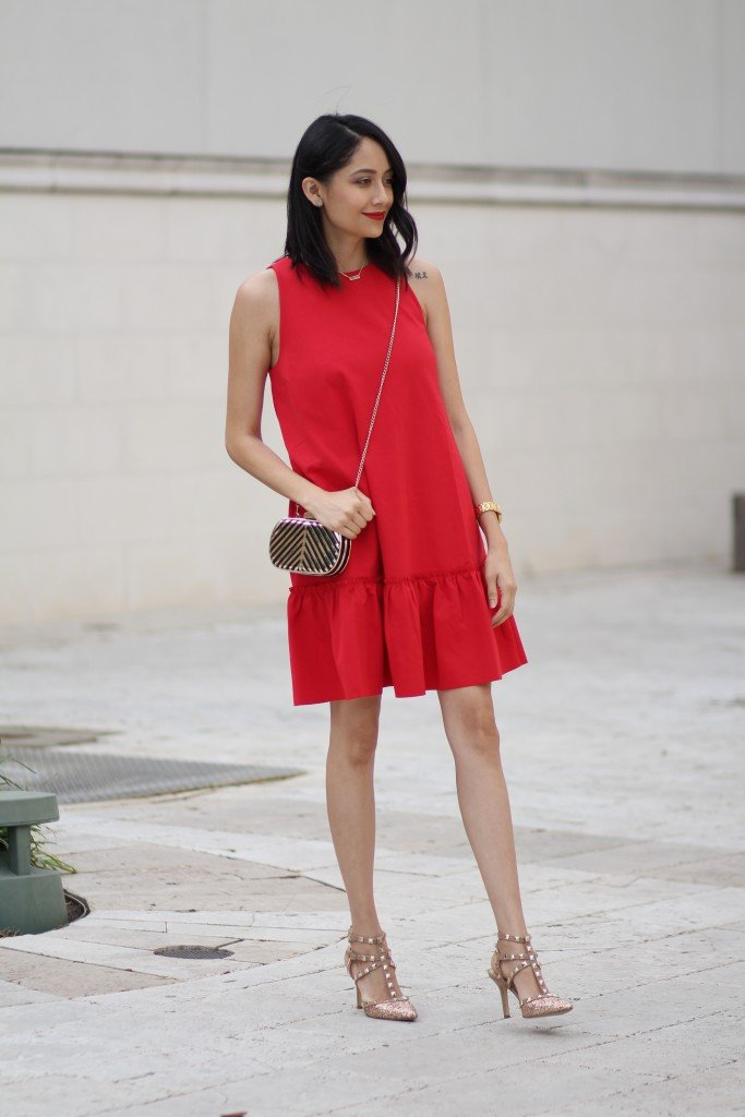 Style blogger Daily Craving wearing a red dress with gold glitter pumps