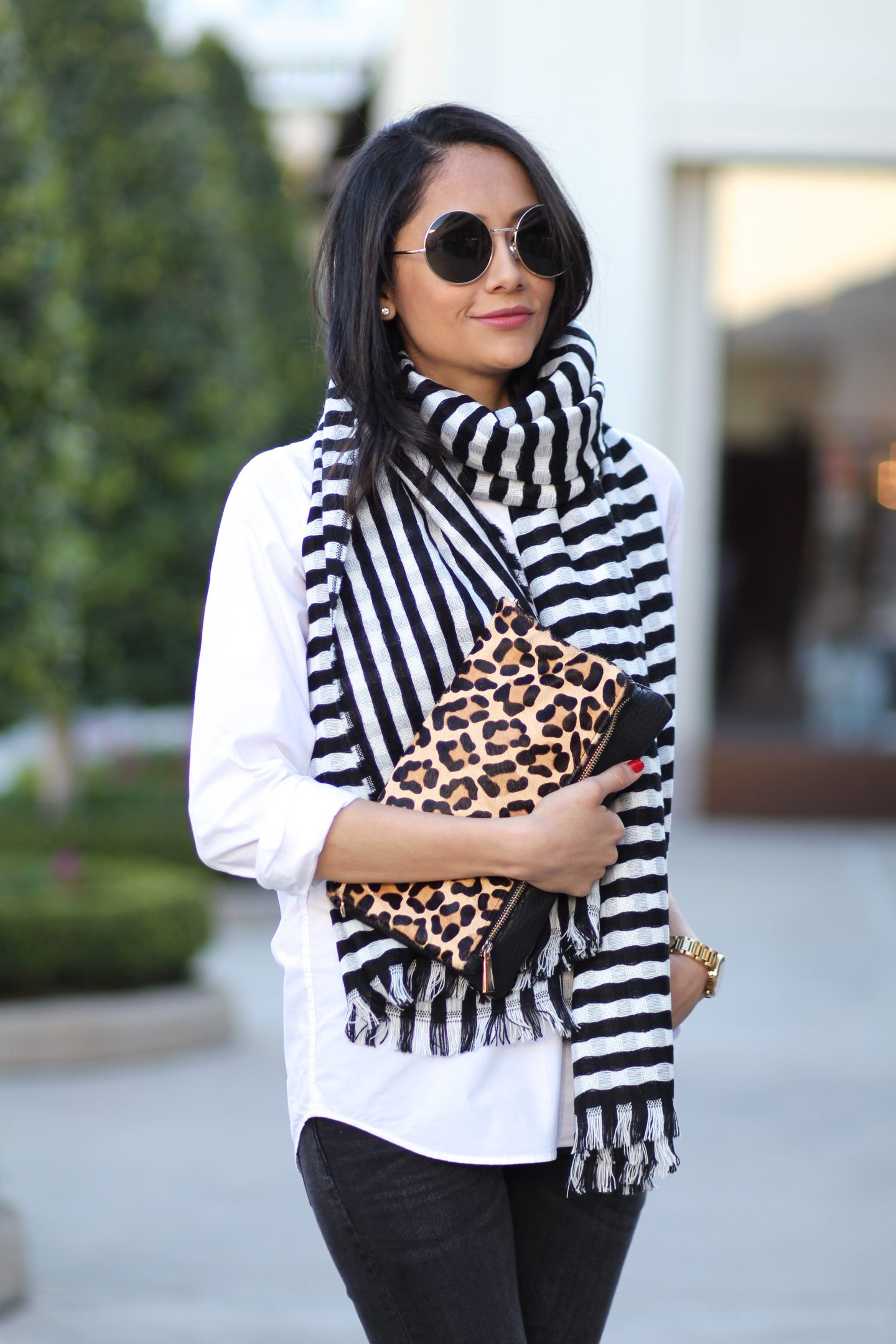 Lifestyle blogger Lilly Beltran wearing a striped scarf and leopard clutch
