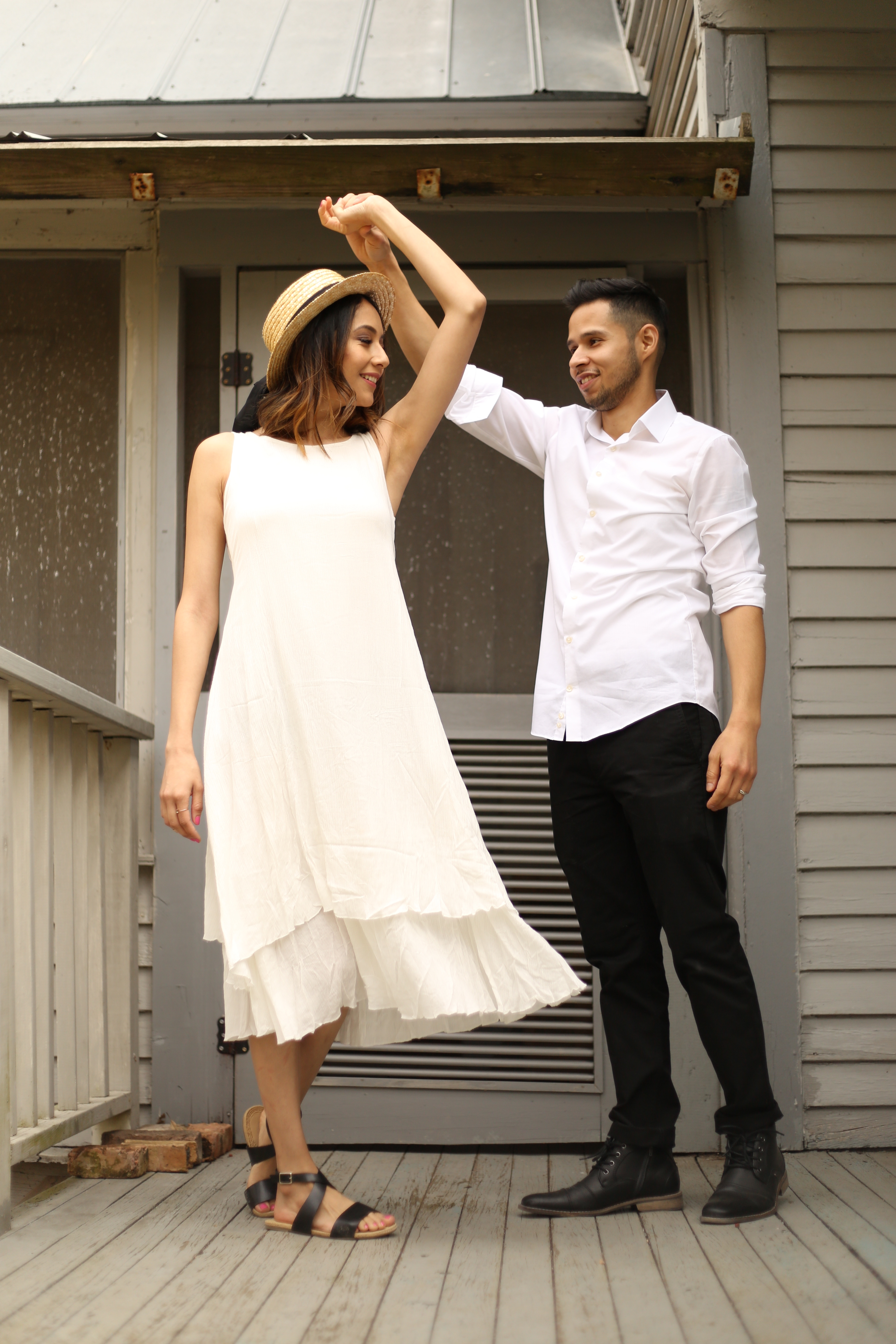 Style blogger Lilly Beltran of Daily Craving dancing with husband Erick in a white dress and boater hat