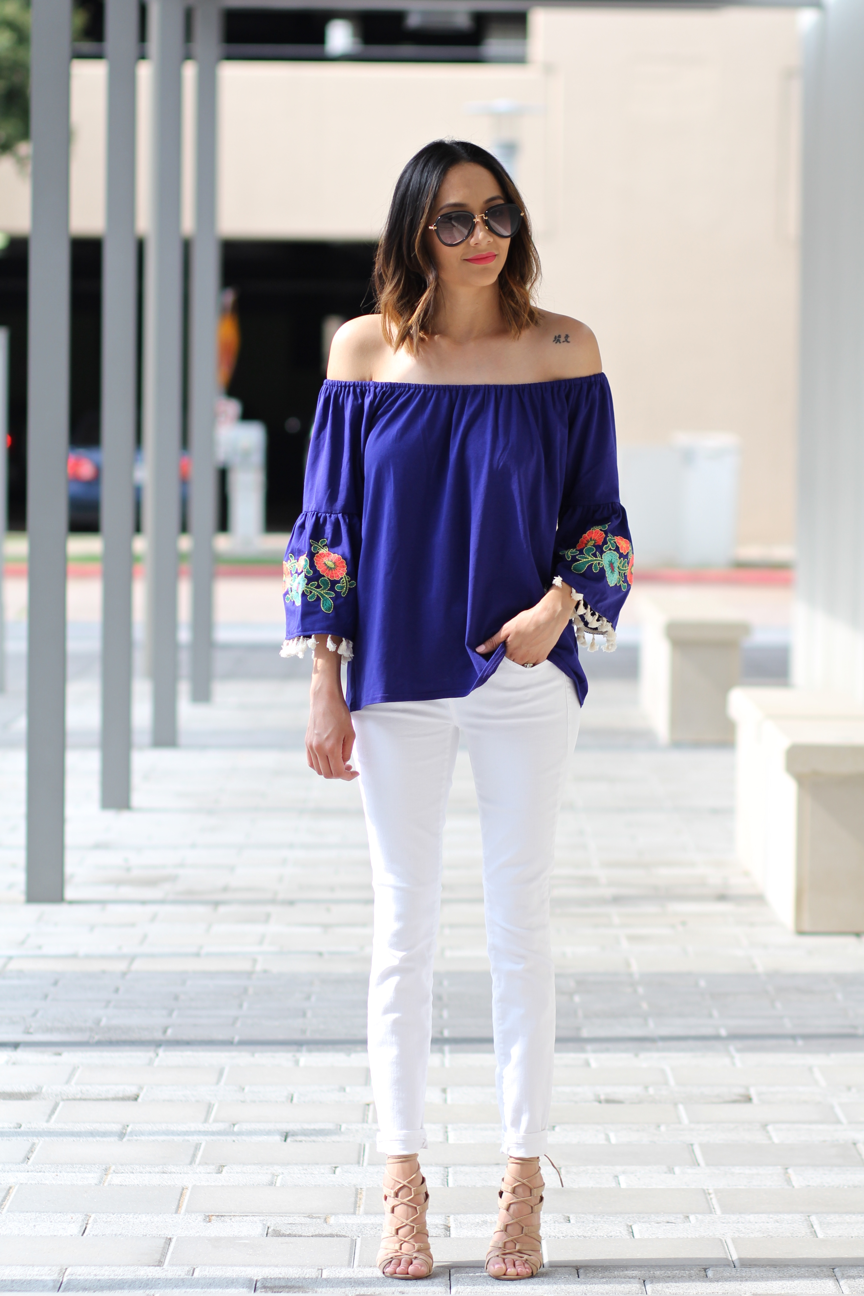 off the shoulder top with embroidered bell sleeves, white jeans and nude heels