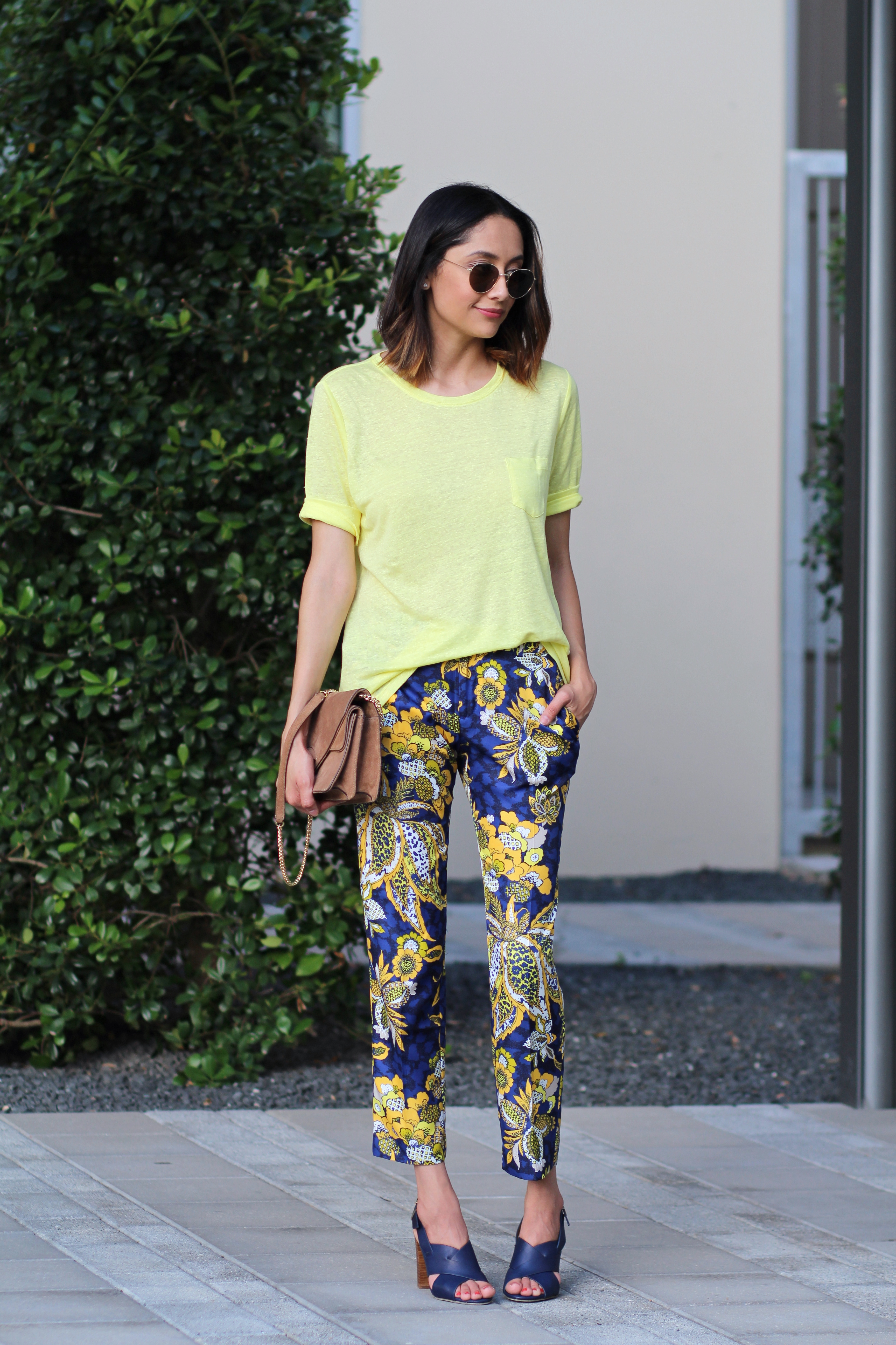 Lilly Beltran of Daily Craving fashion blog in a yellow tee and round sunglasses
