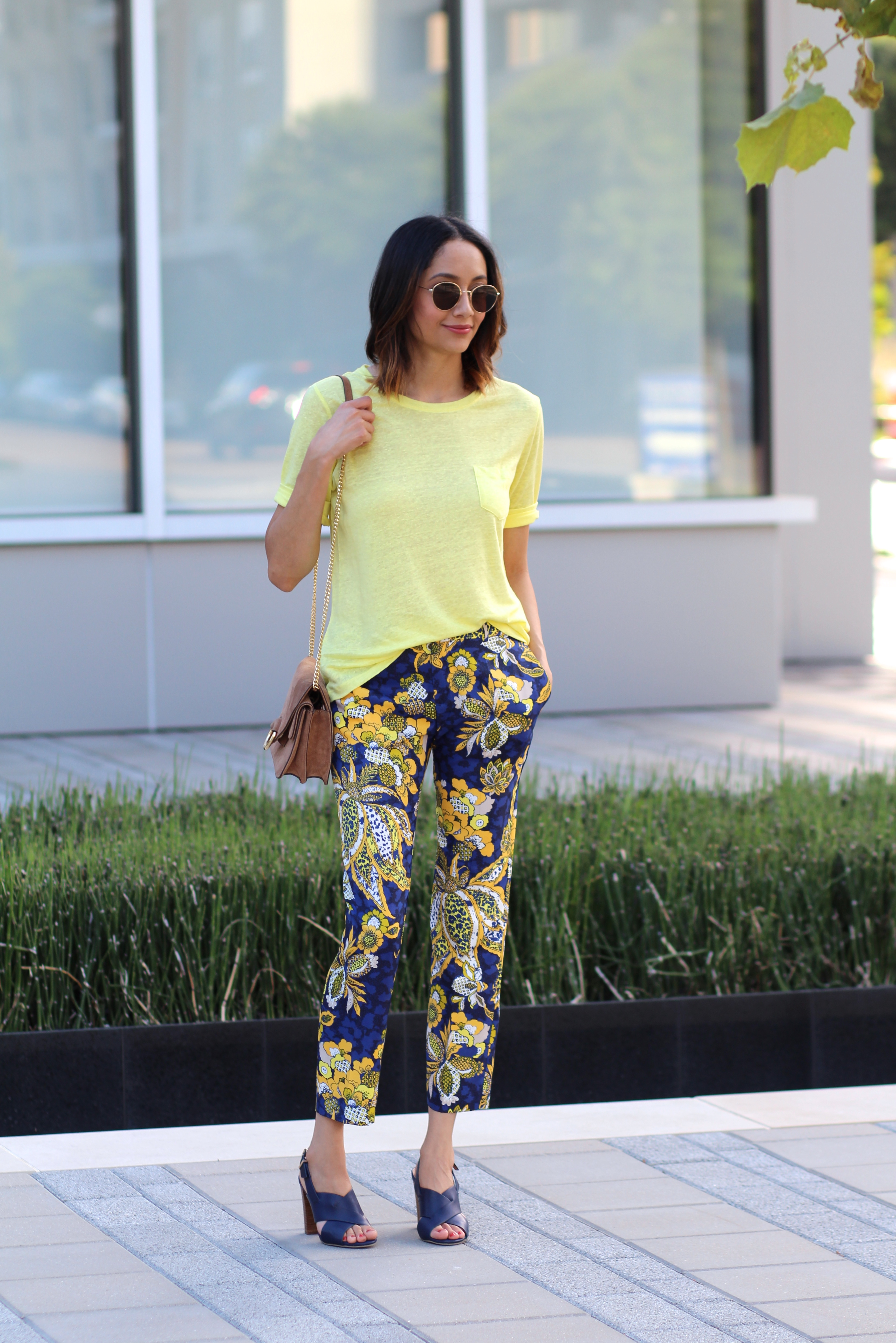 Lilly Beltran of Daily Craving wearing round sunglasses and brown suede purse