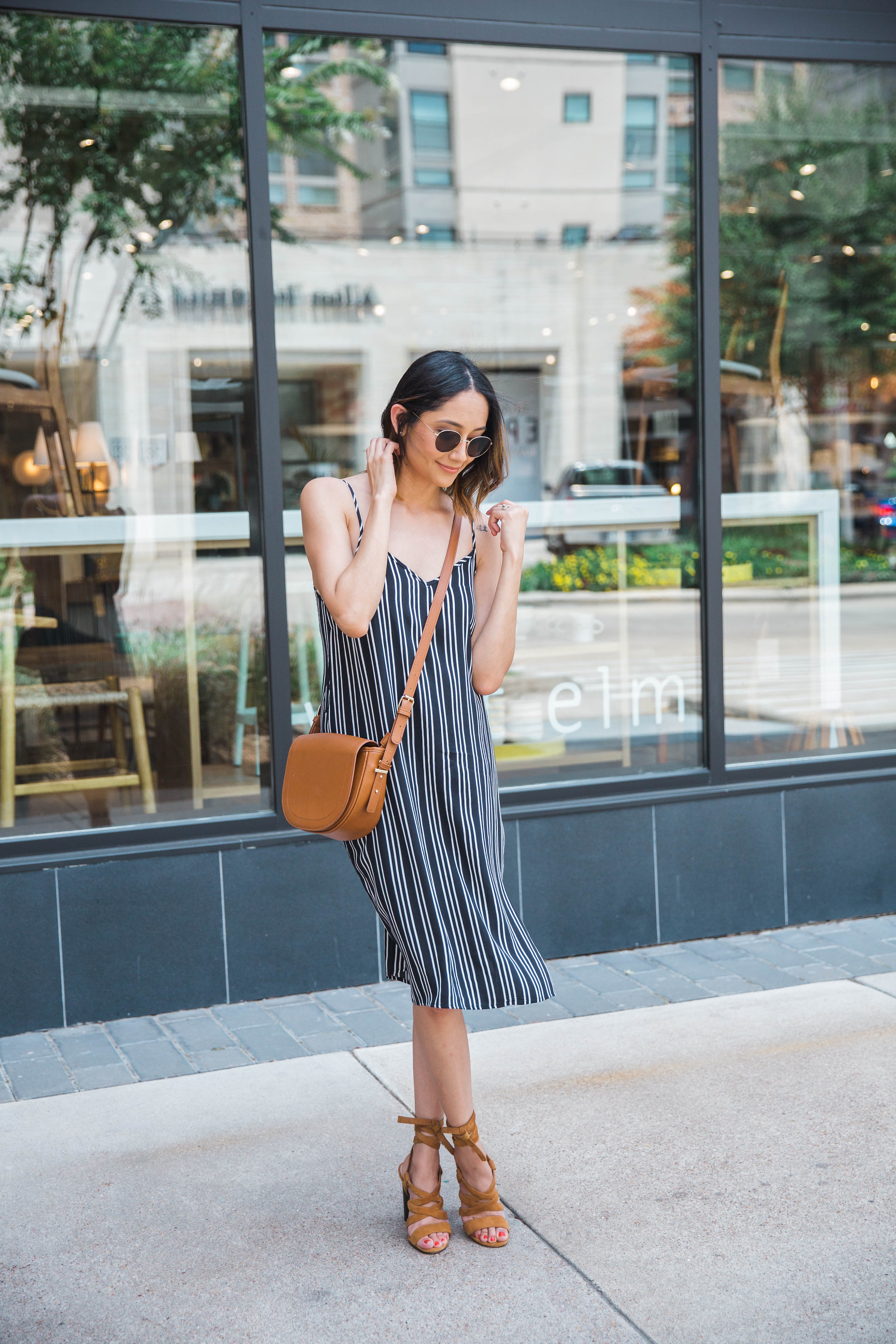 Style blogger Lilly Beltran of Daily Craving in a casual summer outfit with a slip dress and lace-up sandals