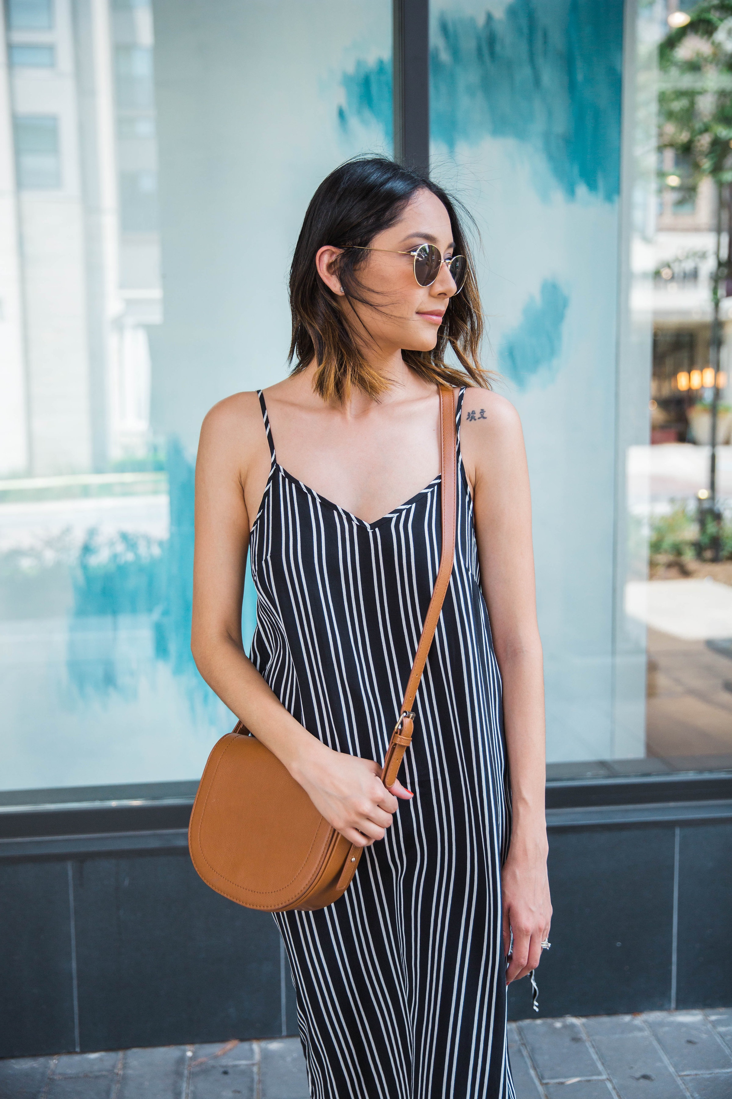 Lilly Beltran of Daily Craving wearing a striped slip dress and round sunglasses