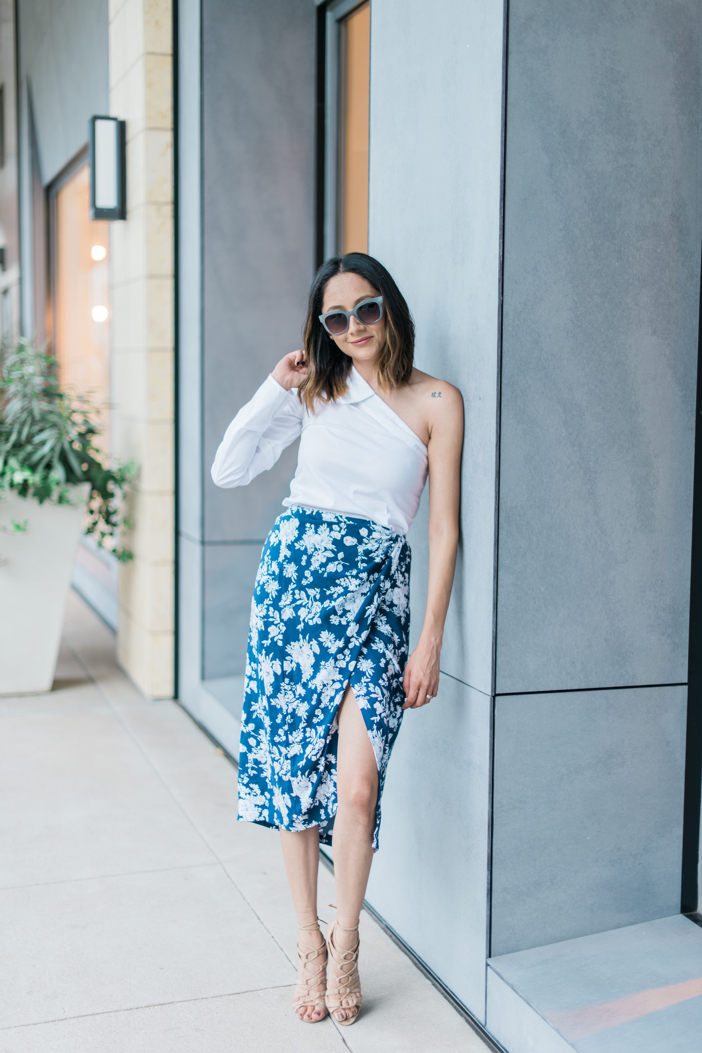 Lifestyle blogger Lilly Beltran of Daily Craving in a summer look wearing a wrap skirt and one sleeve top with nude sandals