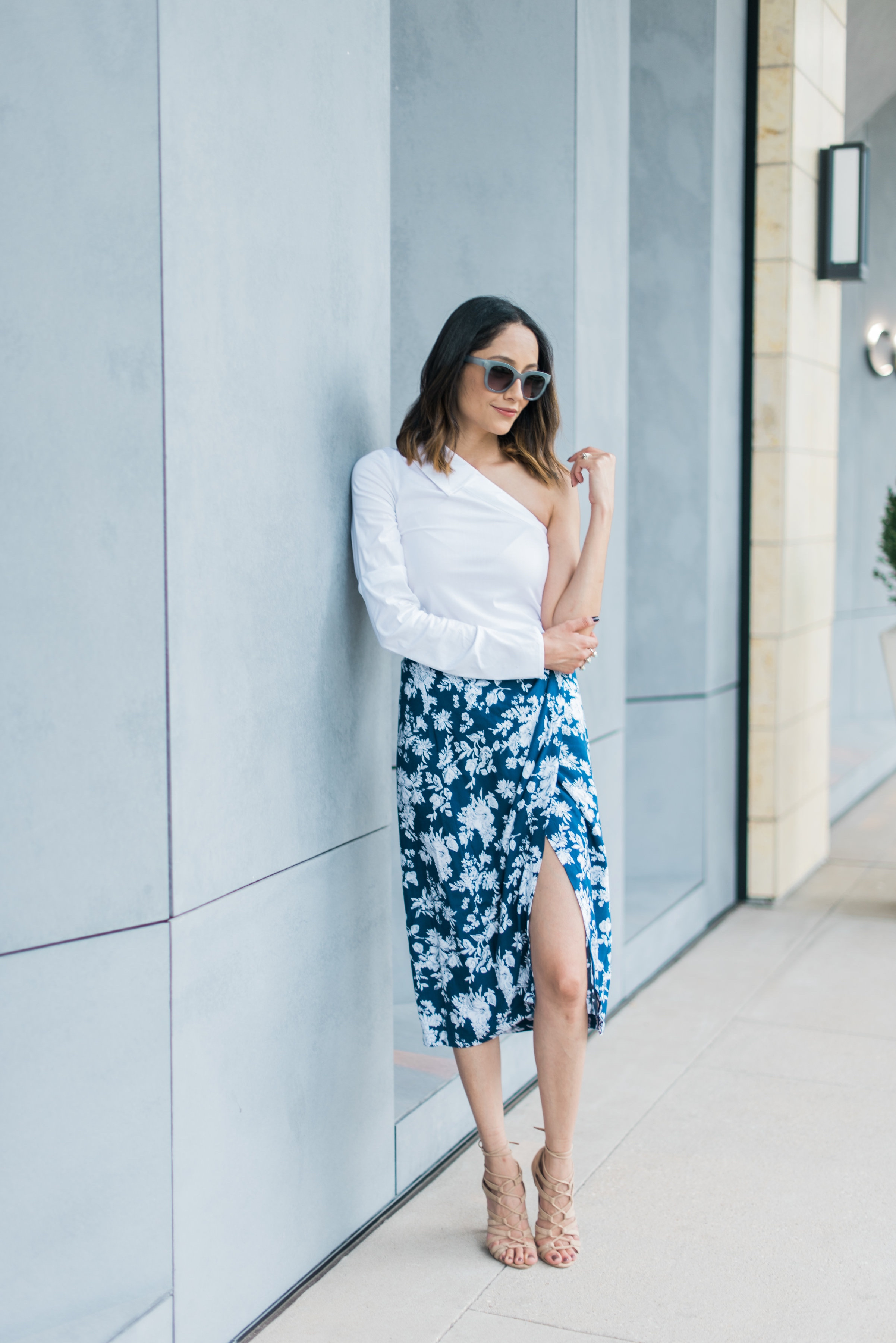 Lifestyle blogger Lilly Beltran of Daily Carving in a summer outfit with a wrap skirt and white one shoulder top