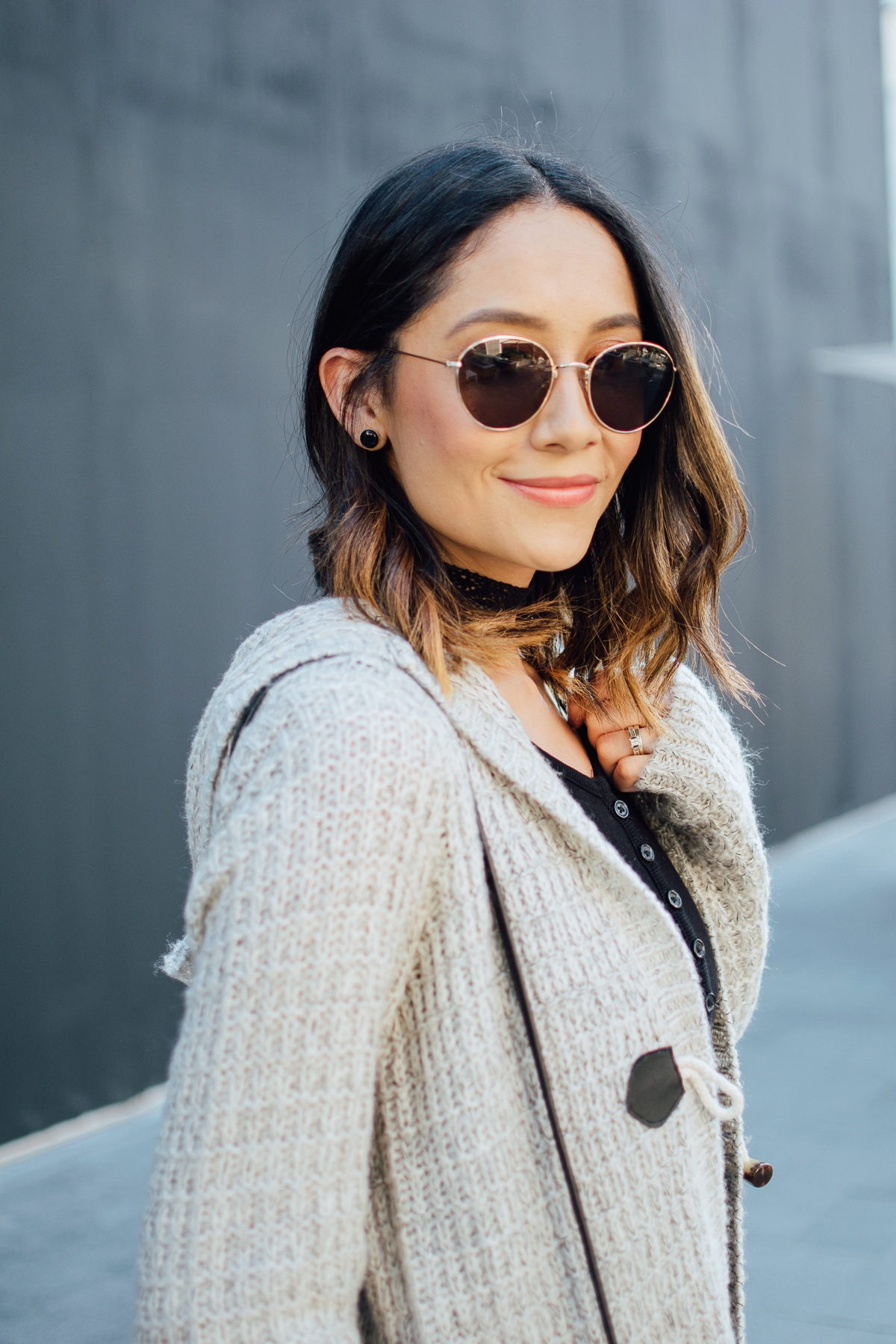 Style blogger Lilly Beltran of Daily Craving in a hooded cardi and round lens sunglasses