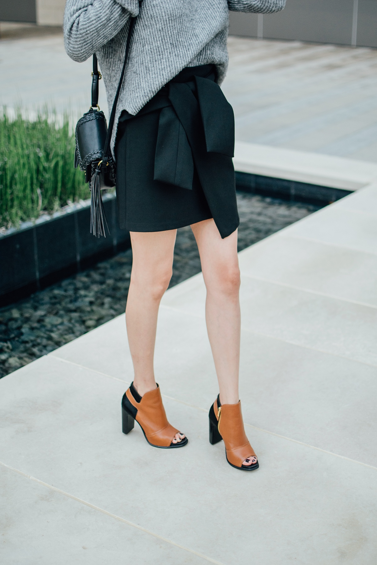 Style blogger Daily Craving wearing M4D3 leather booties with a wrap skirt and grey sweater