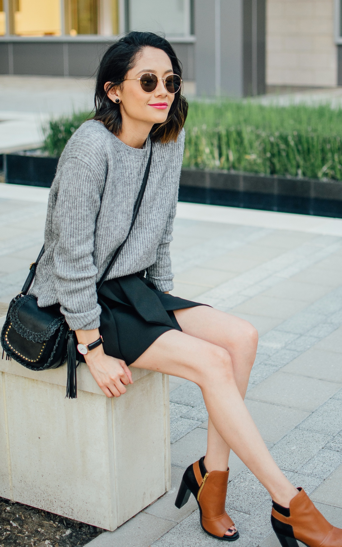 Style blogger Daily Craving styles brown leather booties with a black mini skirt and grey sweater