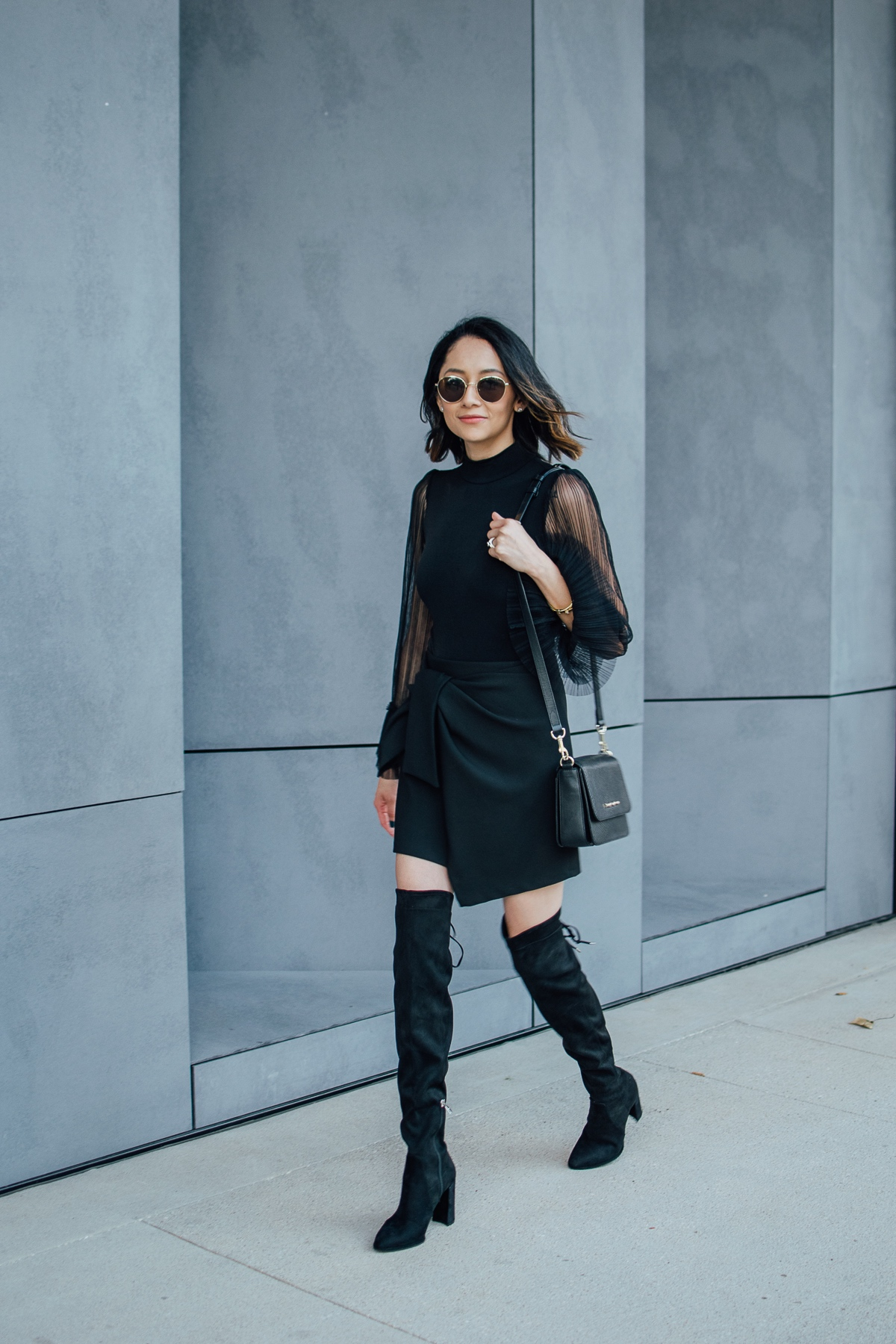 Style blogger Lilly Beltran of Daily Craving in an all black fall look with a bodysuit wrap skirt and OTK boots