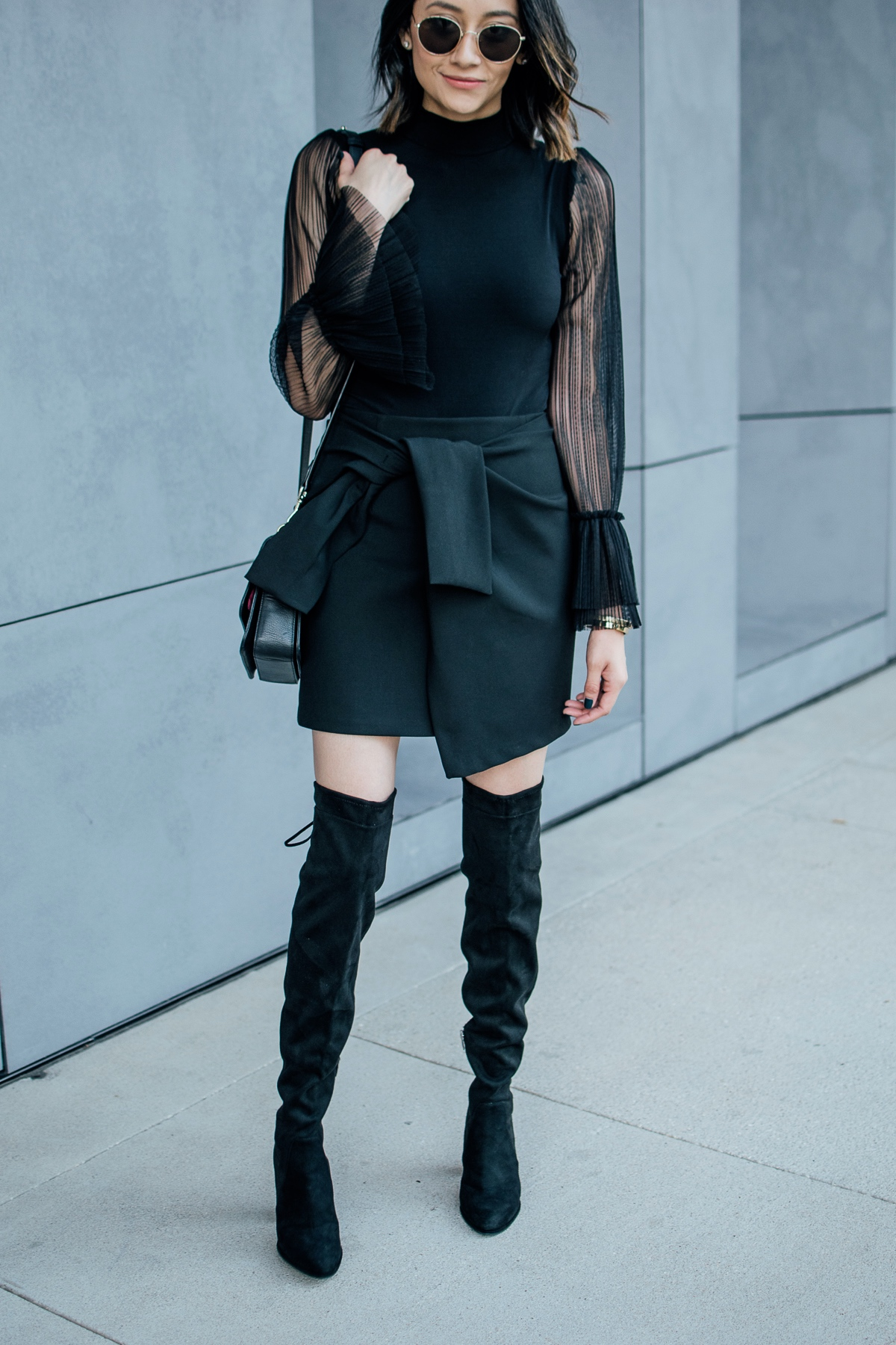 Lilly Beltran of Daily Craving in an all black look with over the knee boots and a wrap skirt