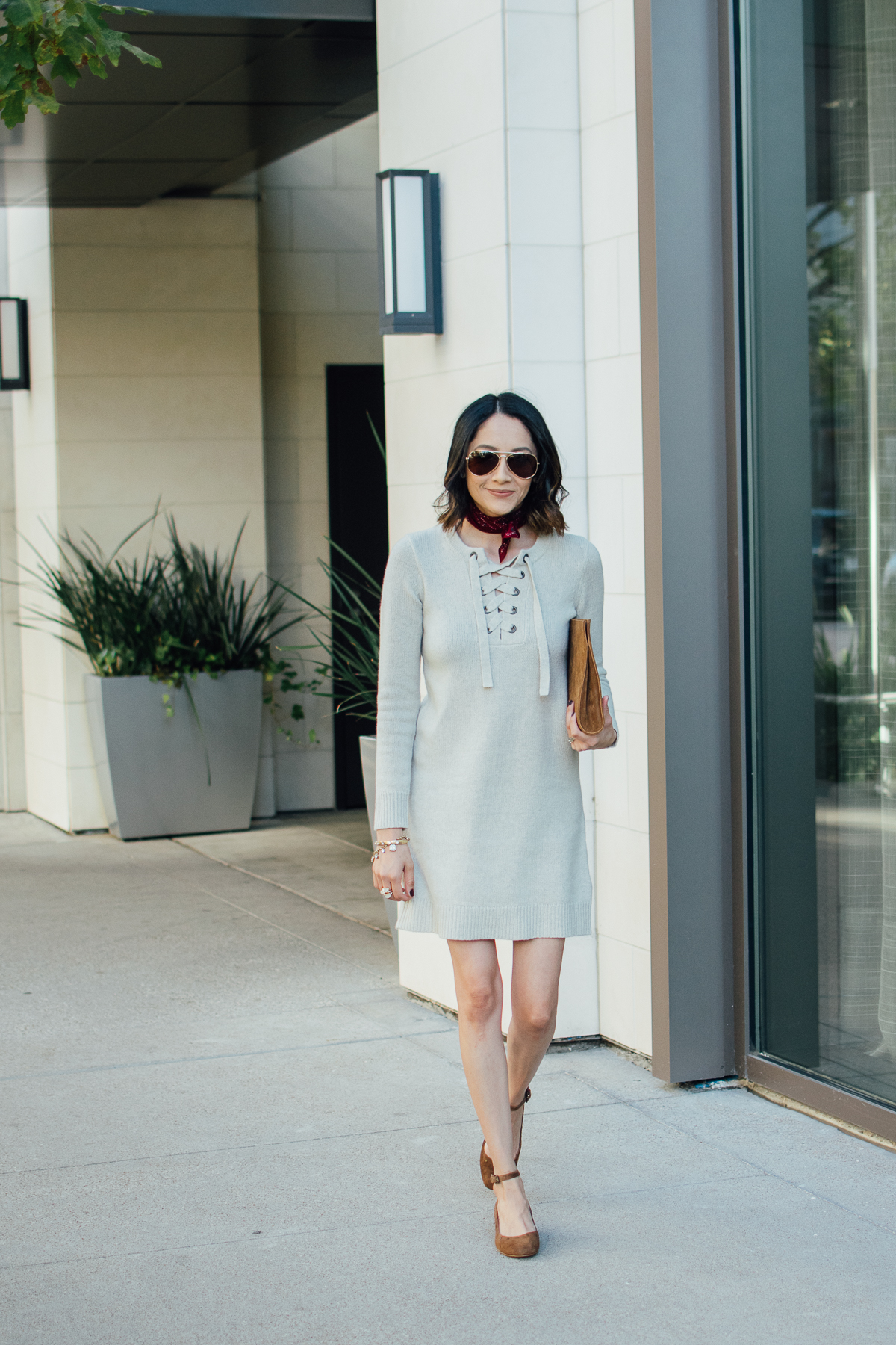 Lilly Beltran of Daily Craving wearing a lace up sweater dress with brown suede shoes and red bandana