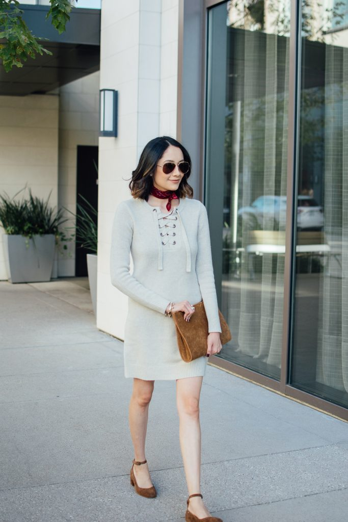 Style blogger Lilly Beltran styles a sweater dress of fall with a neckerchief and suede shoes