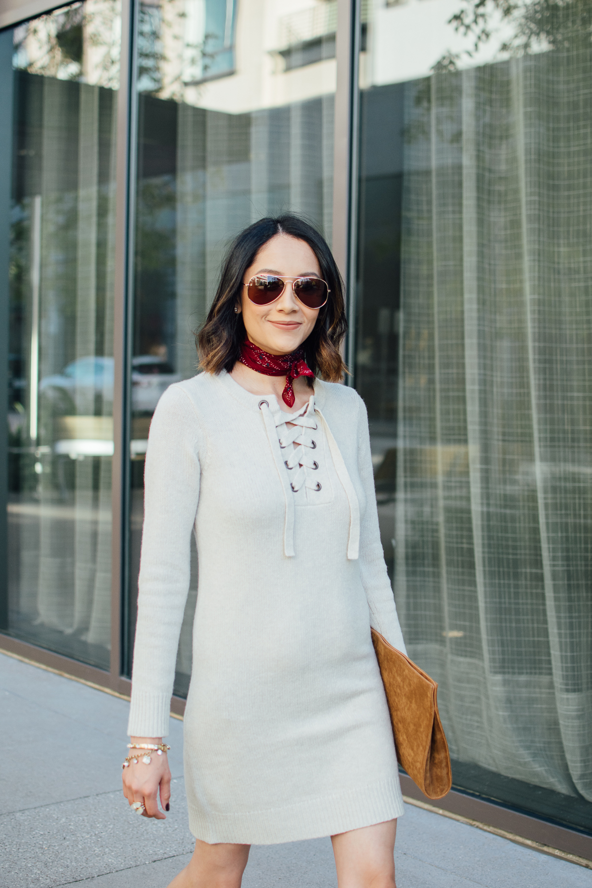 Style blogger Daily Craving wearing a sweater dress with a red neck bandana and aviator sunglasses