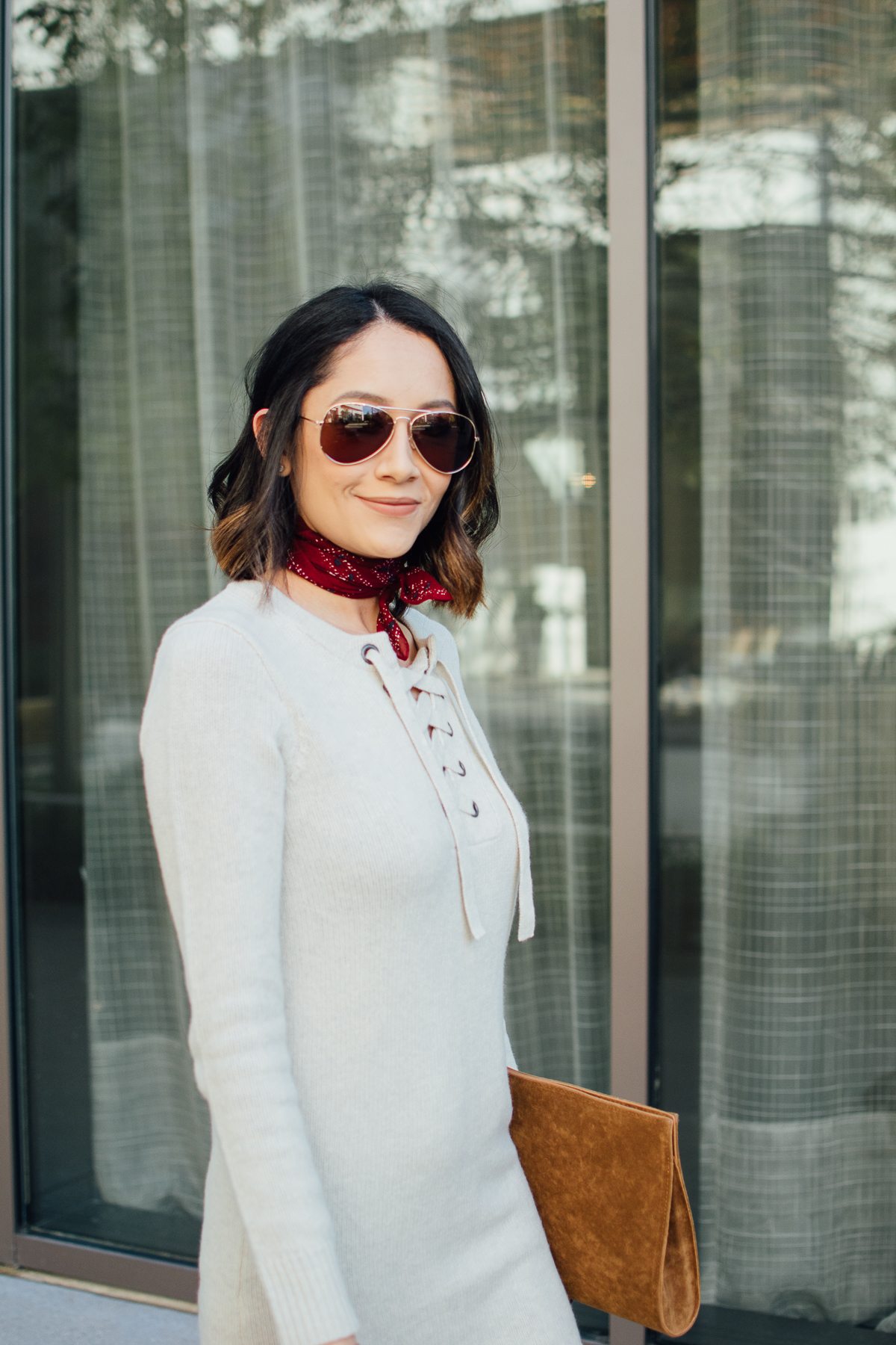Daily Craving wearing a fall outfit with a sweater dress, red bandana and aviators
