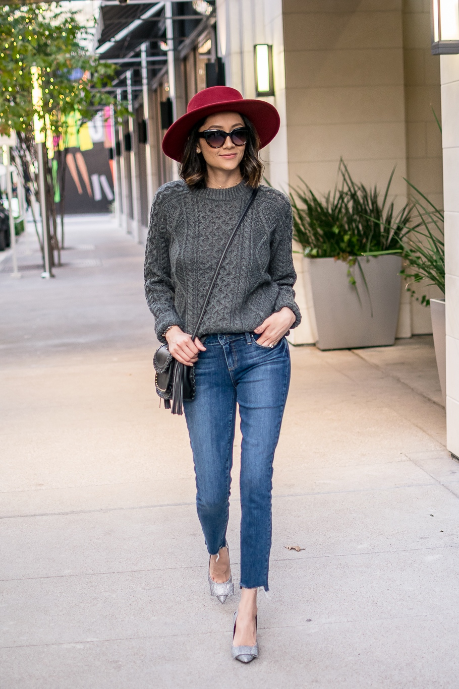 Lilly Beltran of style blog Daily Craving wearing a casual chic Thanksgiving look with a grey cable knit sweater and red hat