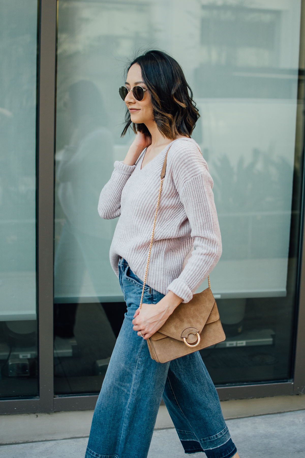 Houston fashion blogger wearing blush wool sweater with wide leg jeans and messy waves
