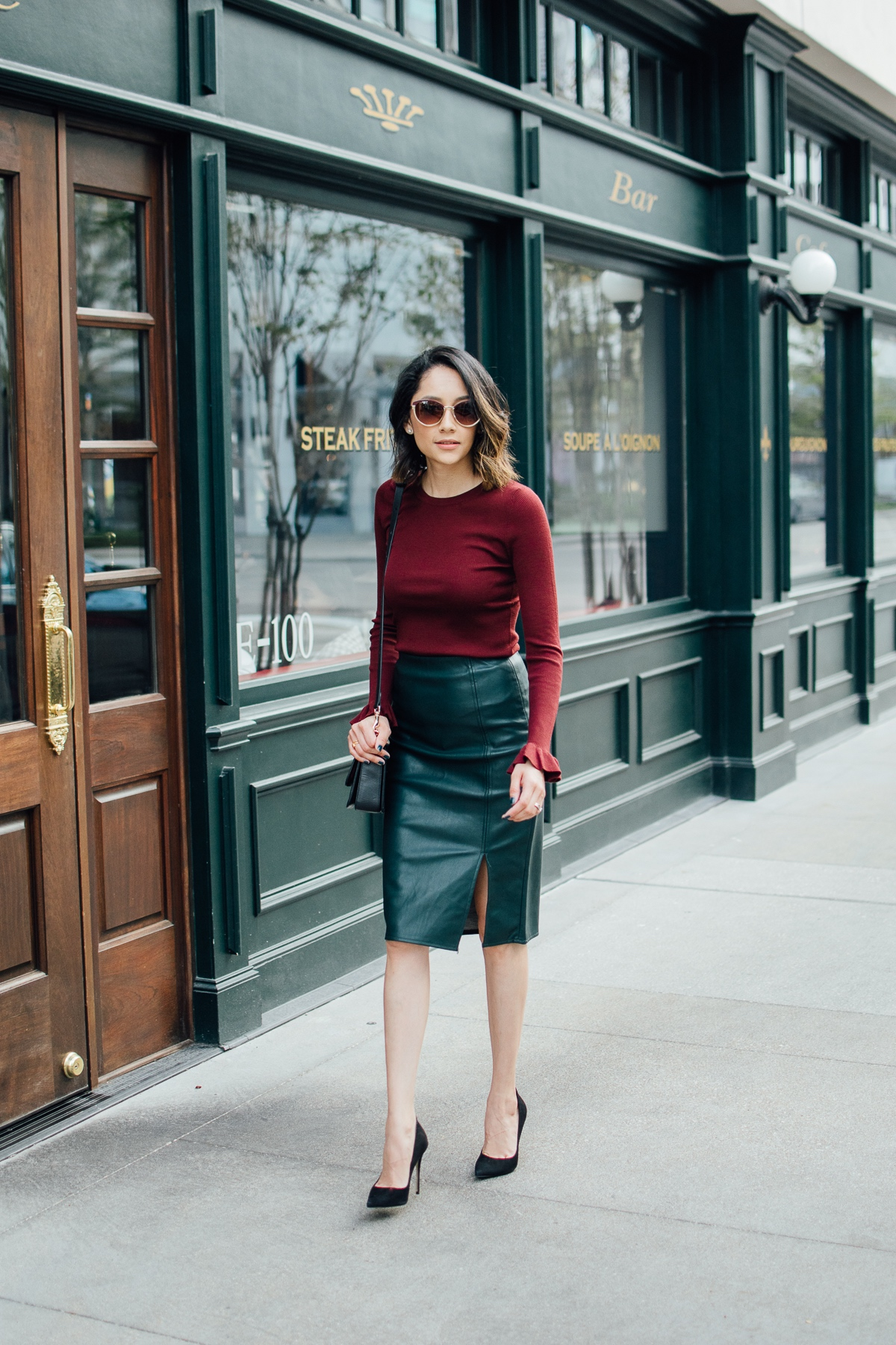 Houston style blogger Lilly Beltran wearing a vegan leather skirt, Burgundy sweater with bell sleeves and black pumps for a holiday ready look
