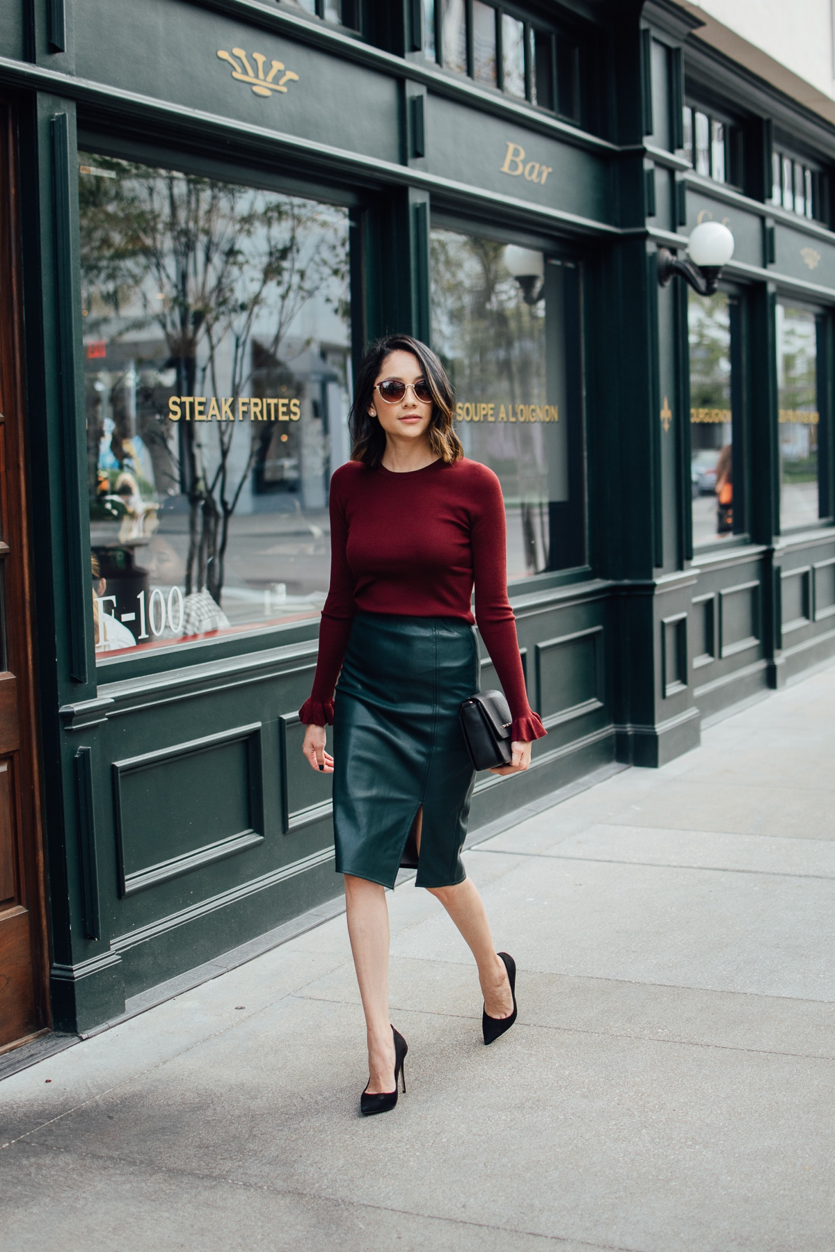 Lilly Beltran of Daily Craving styles a holiday ready look with a green leather skirt and bell sleeve sweater