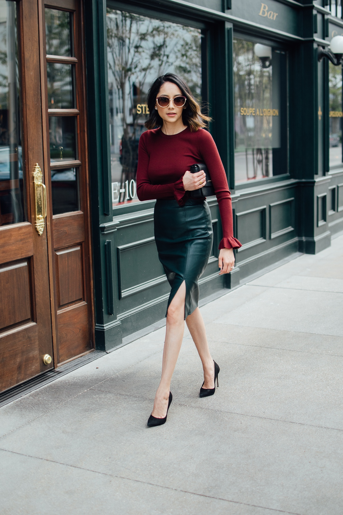 Lilly Beltran of Daily Craving in a holiday ready outfit with a green leather skirt and Burgundy sweater