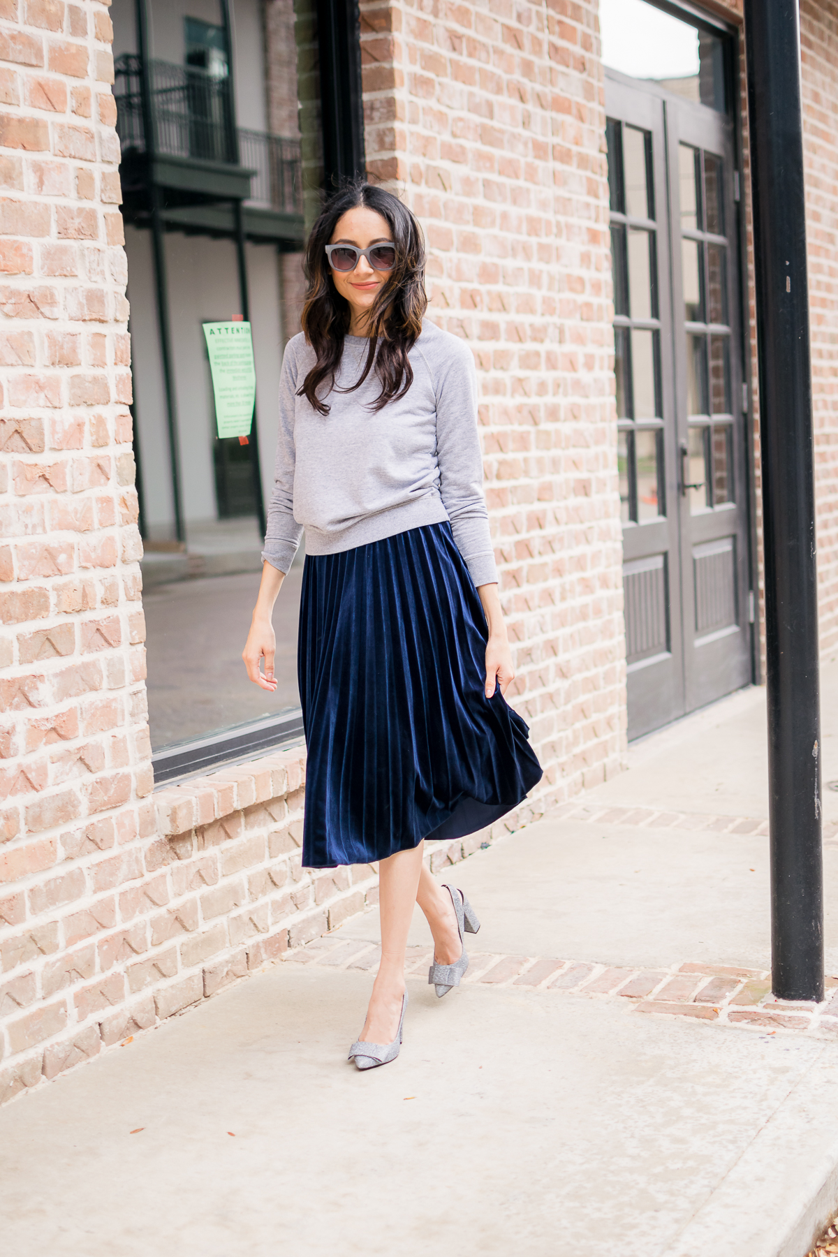 Lilly Beltran of Daily Craving fashion blog wearing a blue velvet skirt with a grey sweatshirt and grey sunglasses