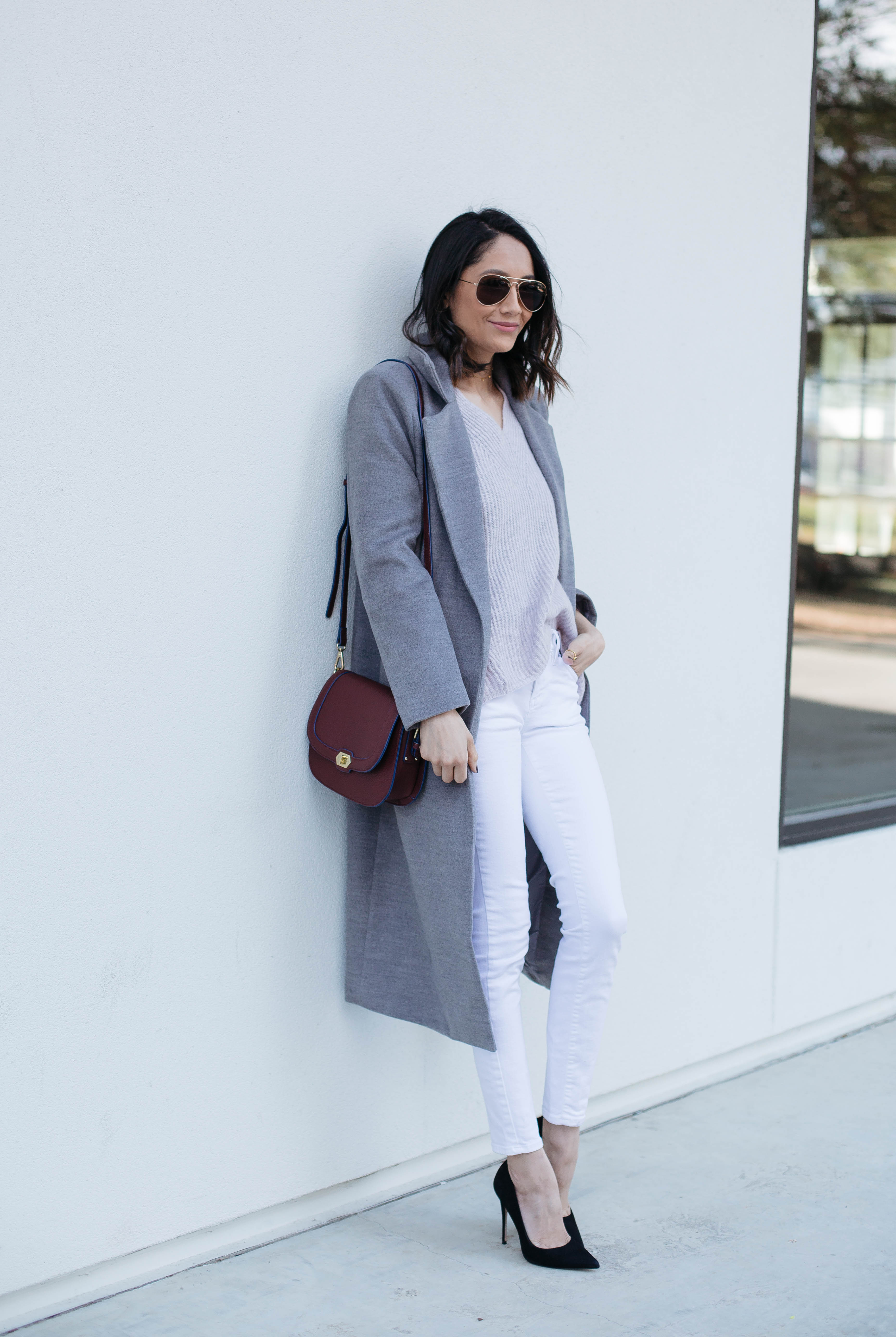 Lifestyle blogger Lilly Beltran of Daily Craving in a chic fall look with a long grey coat and white skinny jeans
