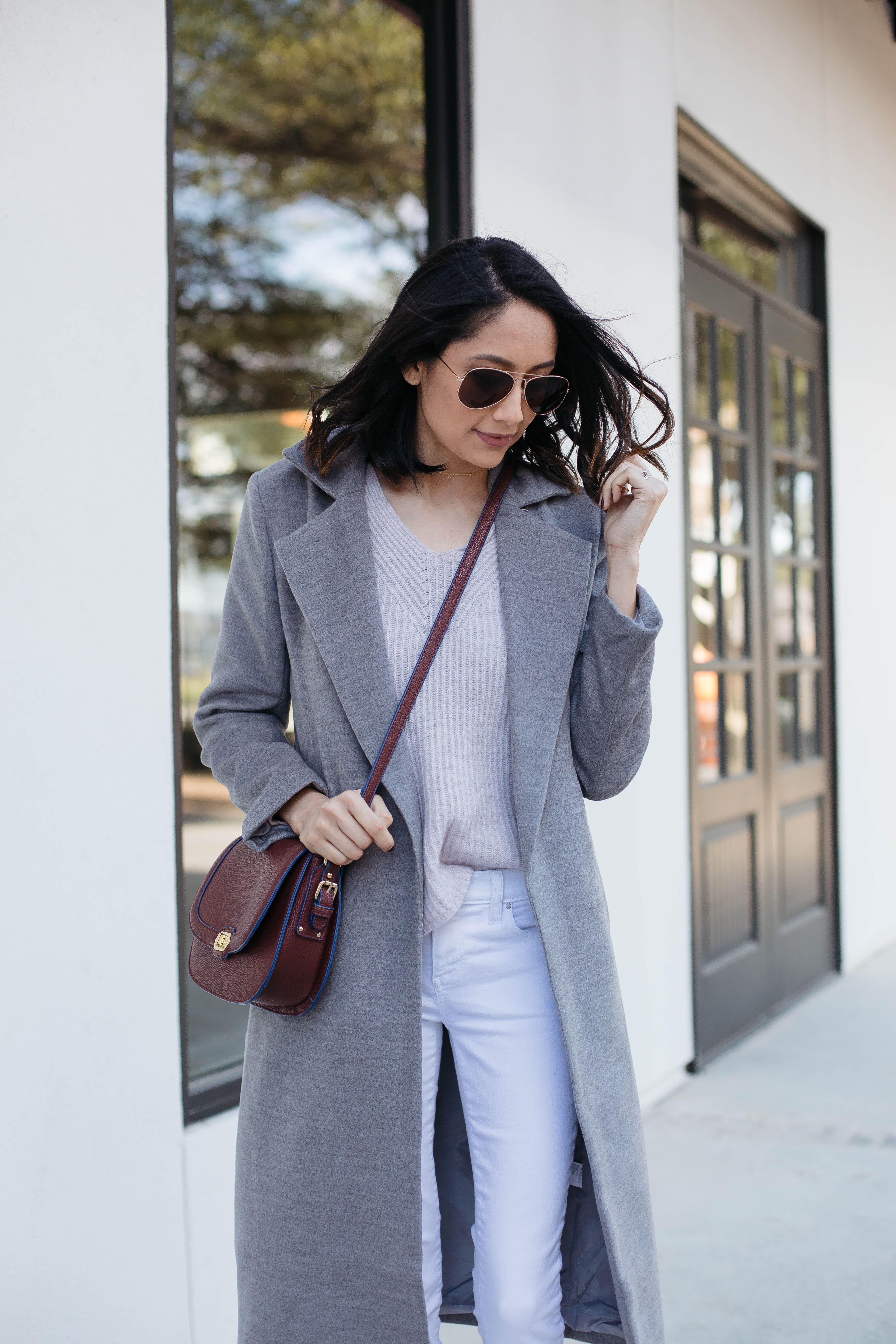 Lifestyle blogger Lilly Beltran of Daily Craving wearing a long grey coat, pink wool sweater and white denim