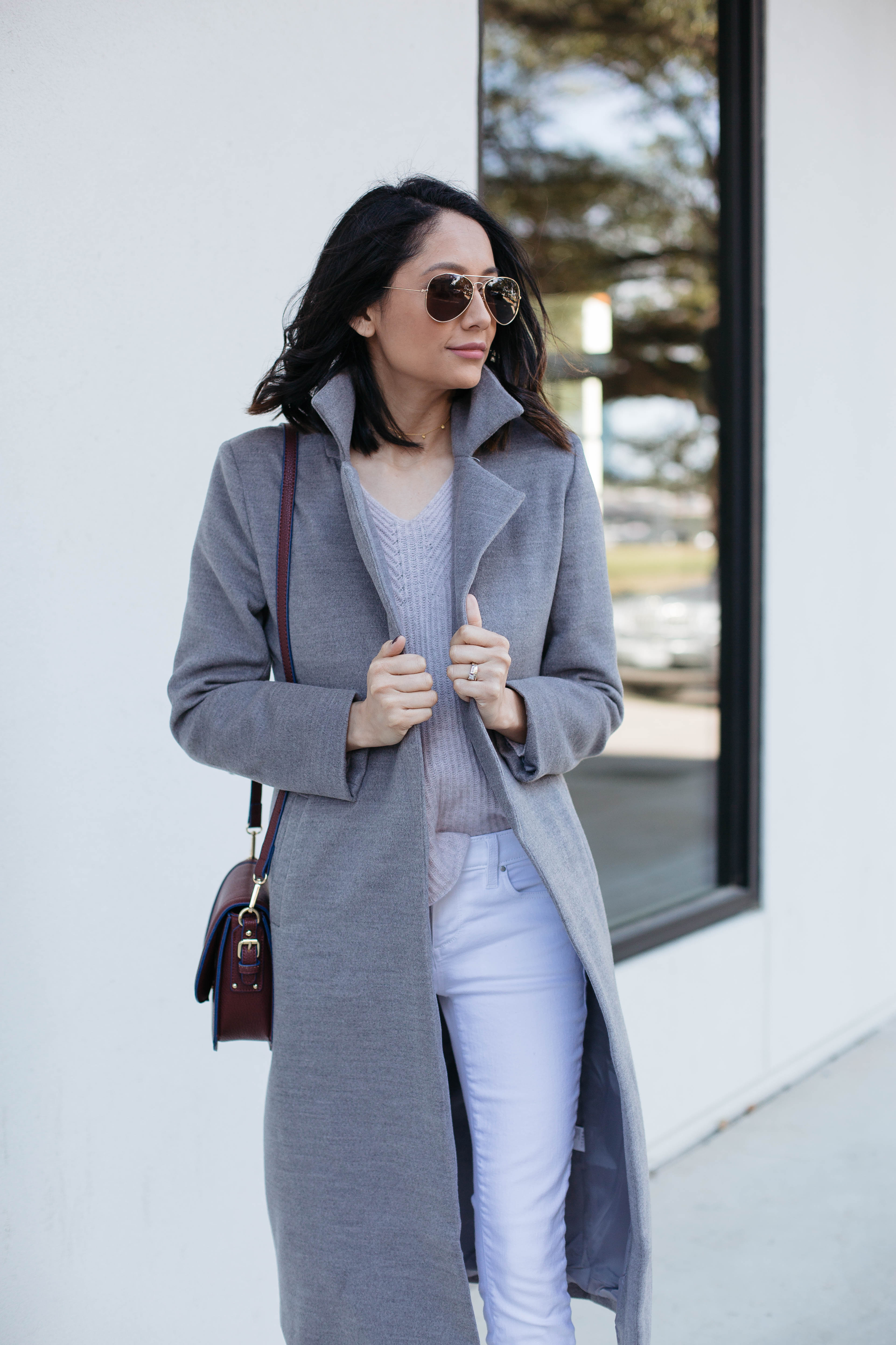 Lifestyle blogger Lilly Beltran of Daily Craving wearing a grey wool coat aviator sunglasses and white skinny jeans